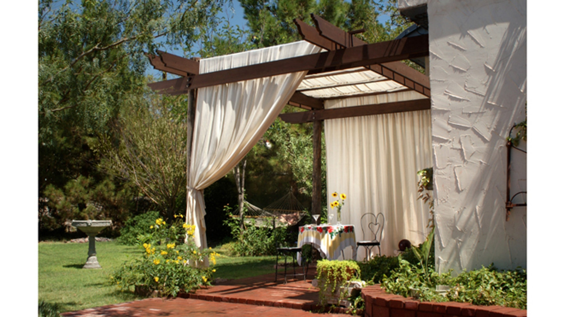 A brick patio with wooden patio posts and a cover of canvas curtains. The back ground has green grass, a birdbath and hammock.