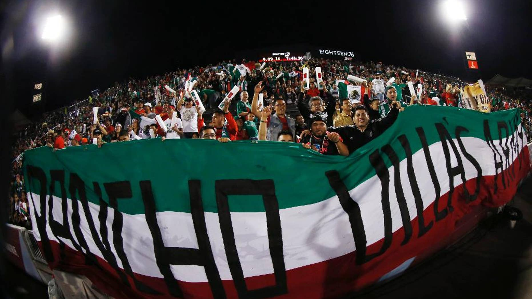 In a photo take with a fisheye lens, fans celebrate as members of the Mexico national team take the field before a 1-0 victory over Bolivia in an international friendly soccer game in Commerce City, Colo., on Tuesday, Sept. 9, 2014. (AP Photo/David Zalubowski)