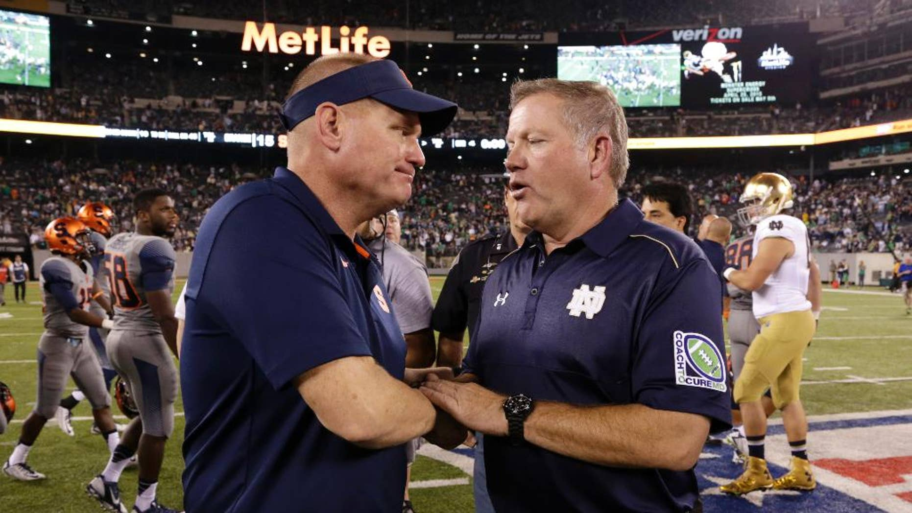 Syracuse coach Scott Shafer, left, and Notre Dame coach Brian Kelly shake hands after an NCAA college football game, Saturday, Sept. 27, 2014, in East Rutherford, N.J. Notre Dame won 31-15. (AP Photo/Julio Cortez)