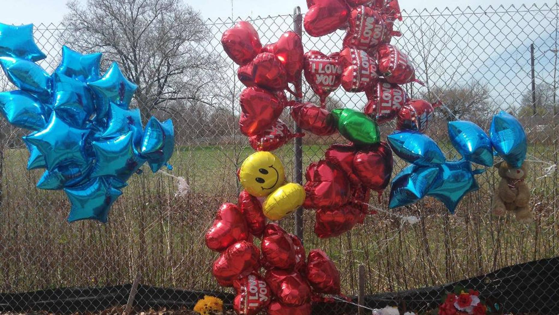 A makeshift memorial sits along a fence Monday, April 17, 2017, near where Robert Godwin Sr., was killed in Cleveland. Police said Steve Stephens killed Godwin on Sunday and posted the video on Facebook. (AP Photo/Mike Householder)