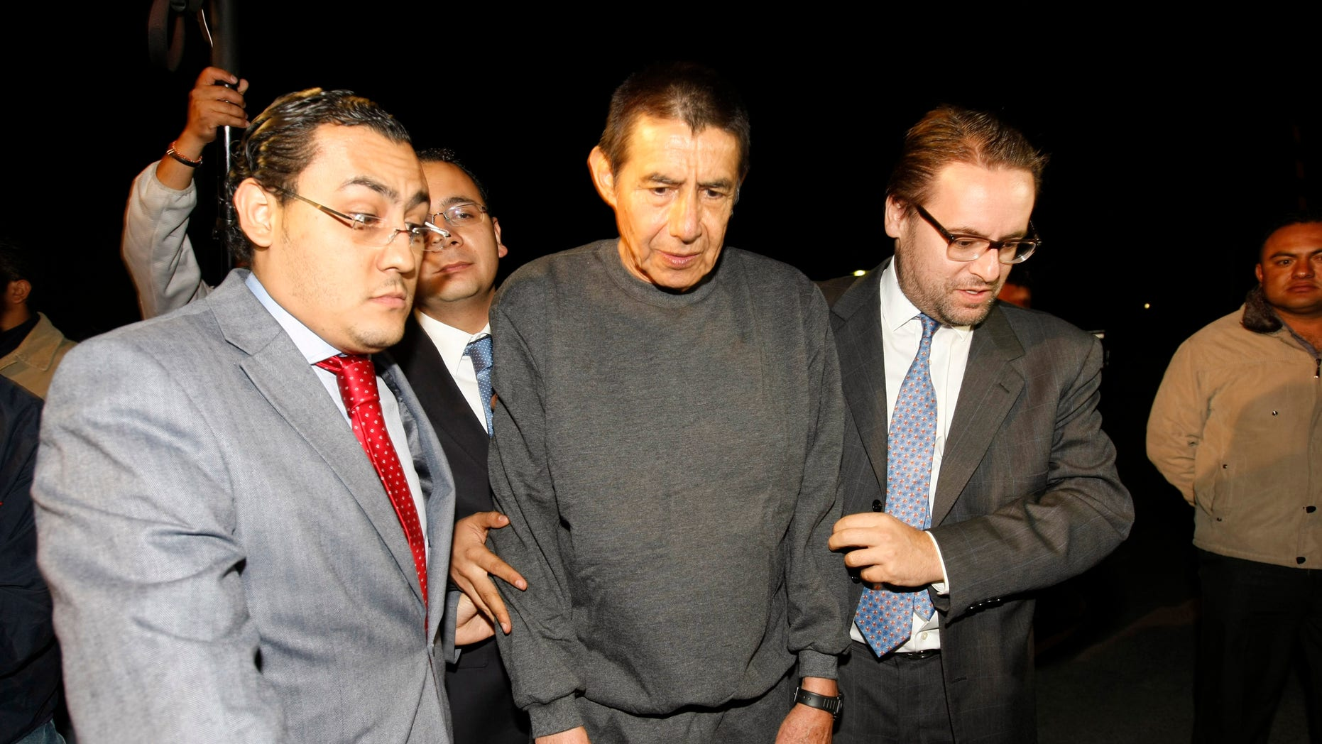 Retired Mexican Army General Tomas Angeles Dauahare, center, is escorted by unidentified members of his legal team as he leaves the Altiplano maximum security prison in Almoloya de Juarez, Mexico, Thursday, April 18, 2013. Federal prosecutors have dropped organized crime charges against Dauahare, accused of aiding a drug cartel after determining that the witness testimony was not enough to sustain their case. He had been in prison since last year, charged with protecting members of the Beltran Leyva cartel. (AP Photo)