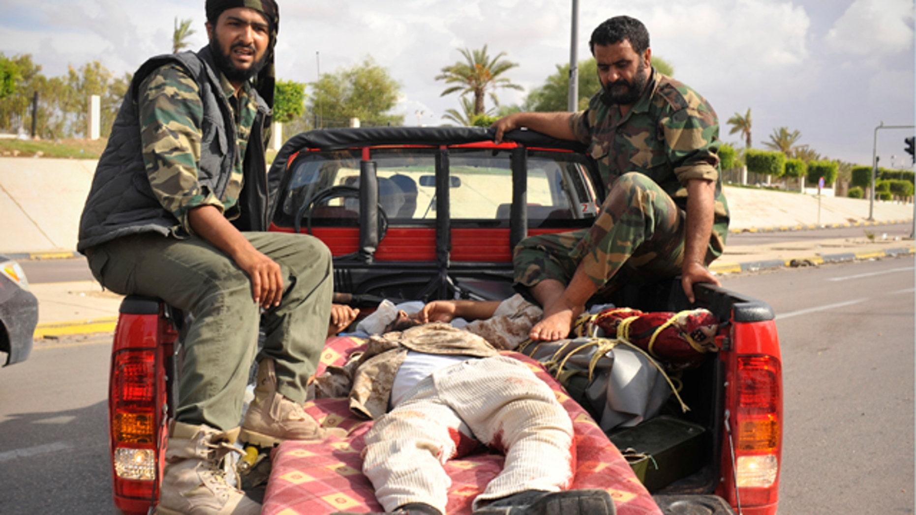 Oct. 13: Libyan revolutionary fighters transport their injured comrade in Sirte, Libya.