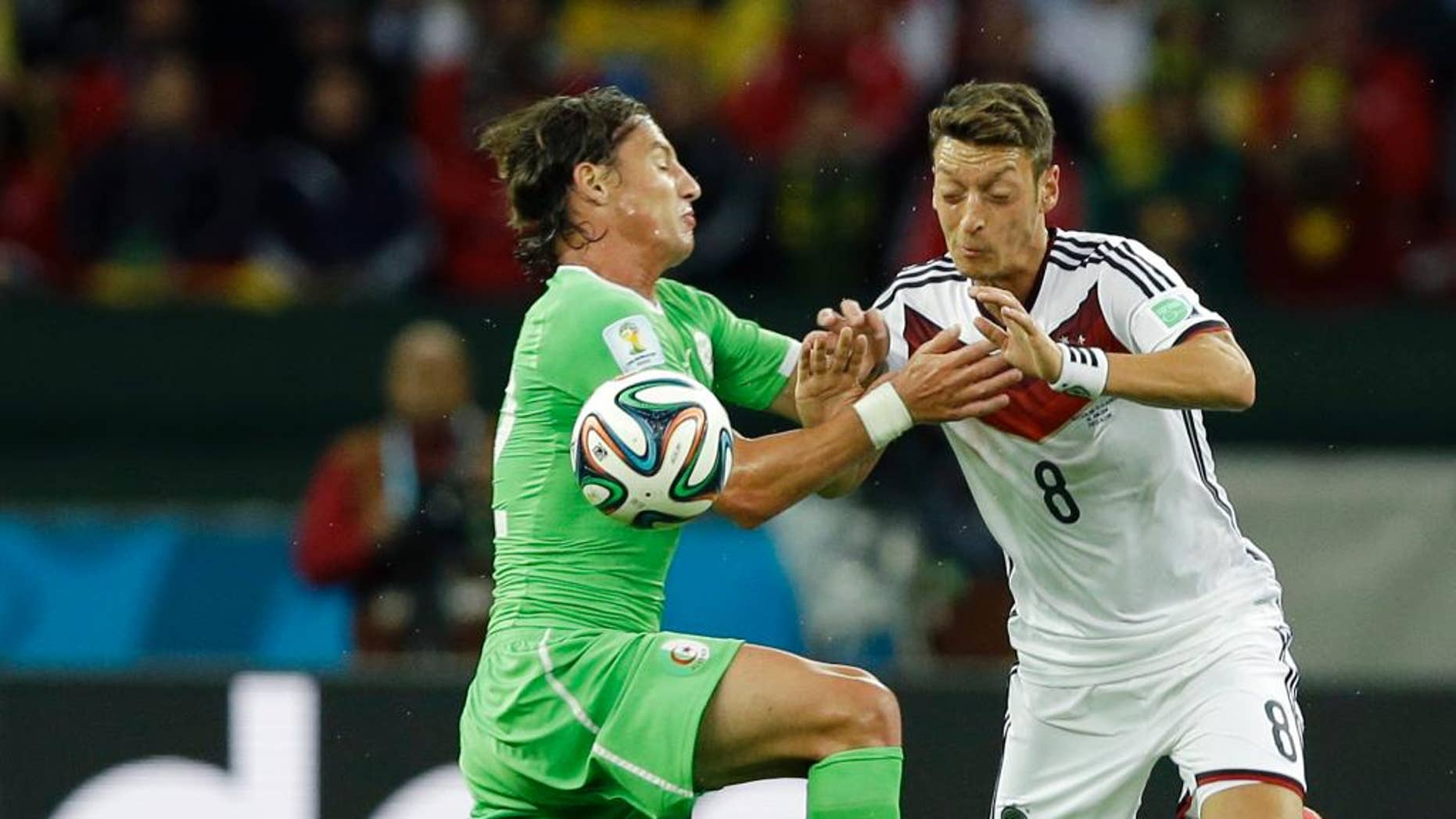 Algeria's Mehdi Mostefa, left, pushes off Germany's Mesut Ozil to stop his attack during the World Cup round of 16 soccer match between Germany and Algeria at the Estadio Beira-Rio in Porto Alegre, Brazil, Monday, June 30, 2014. (AP Photo/Kirsty Wigglesworth)