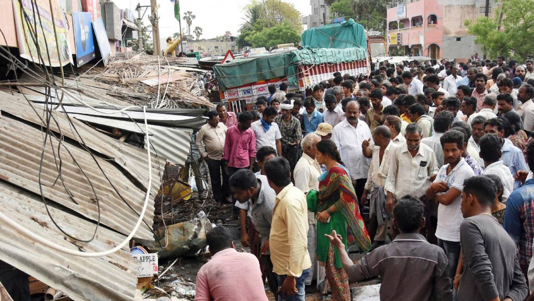 People stand at the site of an accident after a truck driver lost control and plowed into a group of protesting farmers in Yerpedu, in the southern Indian state of Andhra Pradesh, Friday, April 21, 2017. At least a dozen of those killed were electrocuted because the bus first hit an electricity pole causing high-tension wires to fall onto the crowd, police official Jaya Lakshmi said. The farmers were gathered outside the main police station protesting against illegal sand mining in their area. (AP Photo)
