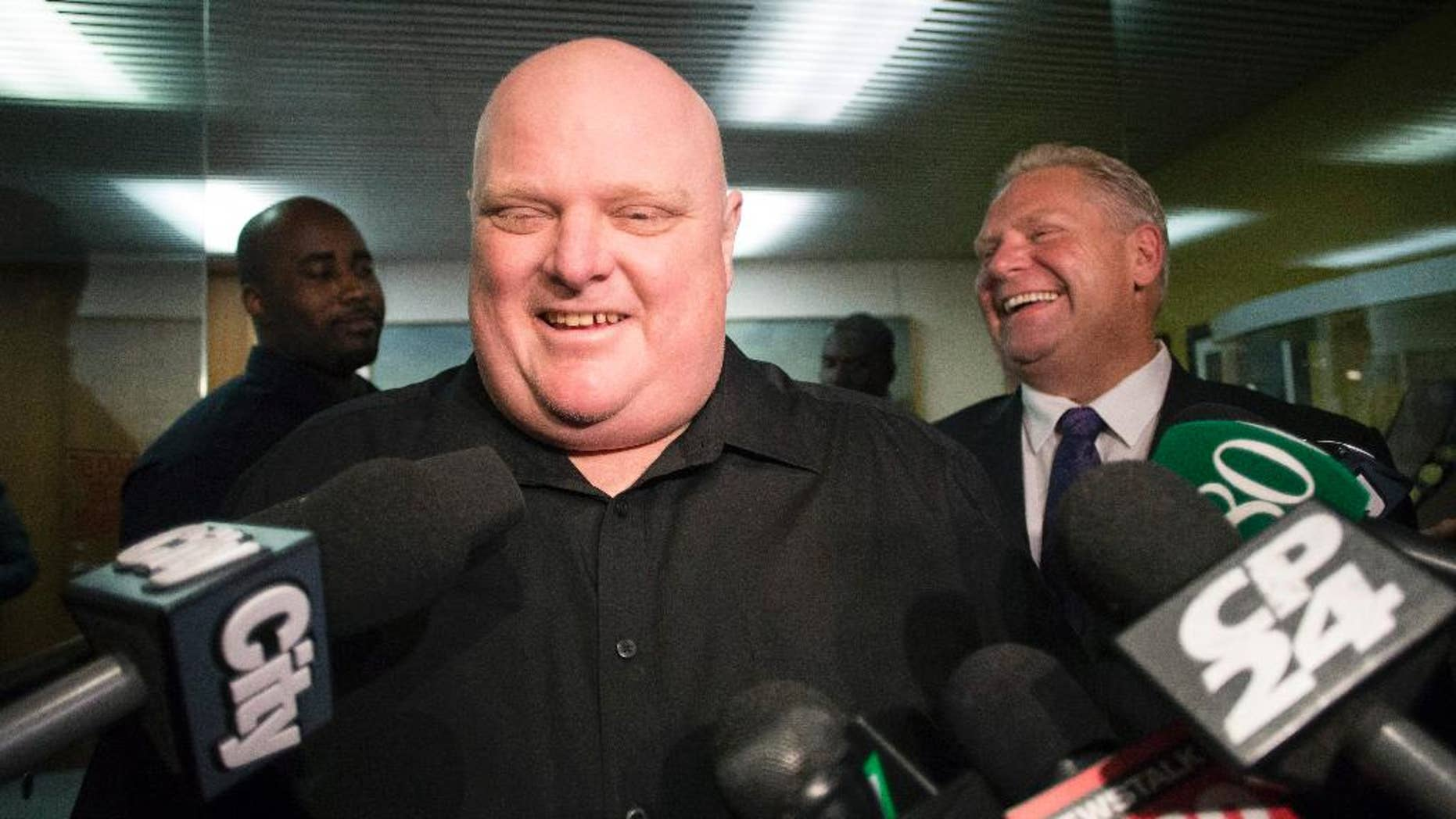 FILE - In this Nov. 21, 2014, file photo, Toronto's outgoing Mayor Rob Ford, front center, stands next to his brother Doug Ford outside his office as he speaks with the media before signing bobblehead dolls in in his likeness in Toronto. The notorious former Toronto mayor and now city councilor is auctioning off some of the memorabilia he has collected over the years. Ford's term was plagued by scandals involving drinking, crack cocaine use and erratic behavior. (AP Photo/The Canadian Press, Chris Young, File)