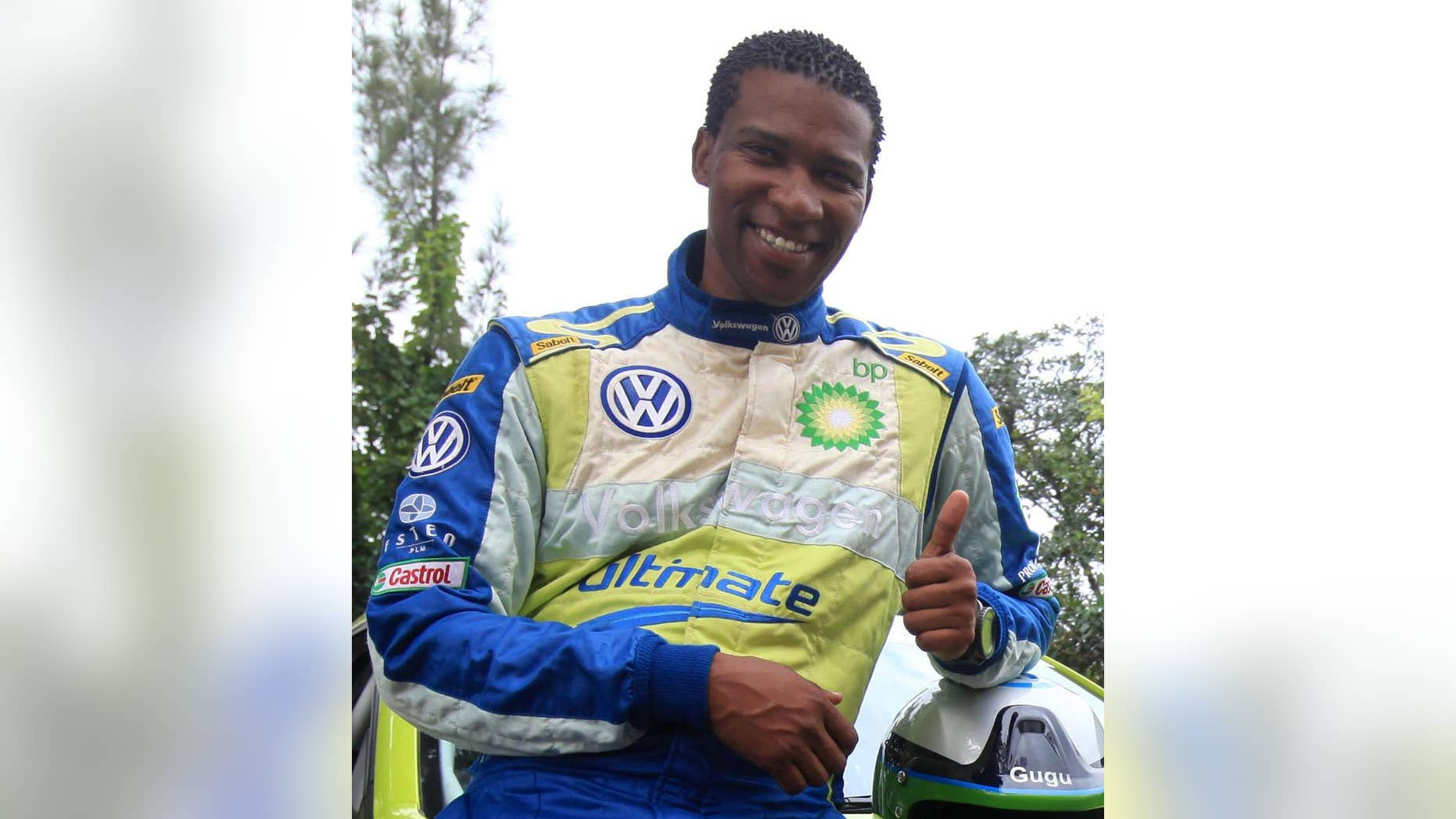 """In this photo taken in 2011, South Africa rally driver Gugu Zulu gestures next to his car. A South African trying to summit Kenya's Mount Kilimanjaro to mark Mandela Day has died. A statement from the Nelson Mandela Foundation said details are """"sketchy"""" but that it appeared Gugu Zulu had problems breathing early Monday July 18, 2016, as his group tried to reach Africa's highest peak. (AP Photo)"""