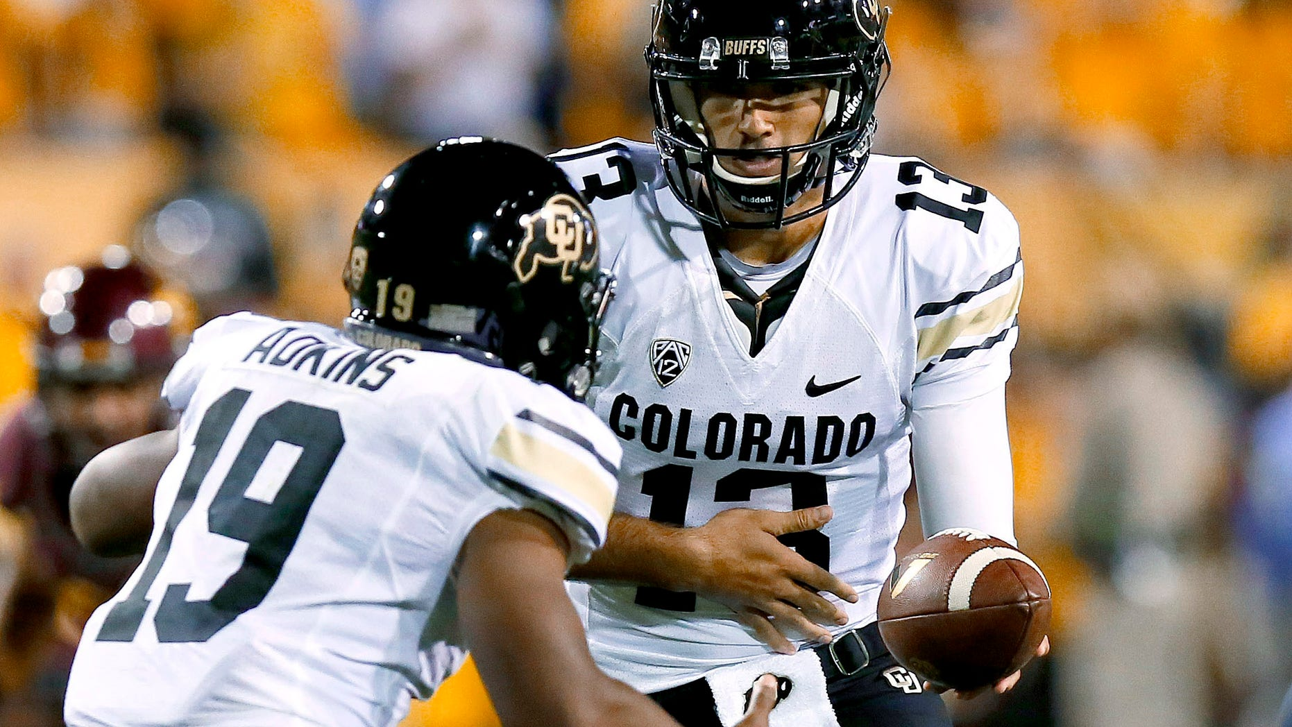 FILE - In this Oct. 12, 2013, file photo, Colorado's quarterback Sefo Liufau (13) hands the ball off to Michael Adkins II (19) during the first half of an NCAA college football game against Arizona State in Tempe, Ariz.  Liufau, a freshman, gets his first start Saturday when Colorado hosts lower-tier but unbeaten Charleston Southern, a fill-in for their flooded-out game against Fresno State last month. (AP Photo/Ross D. Franklin, File)