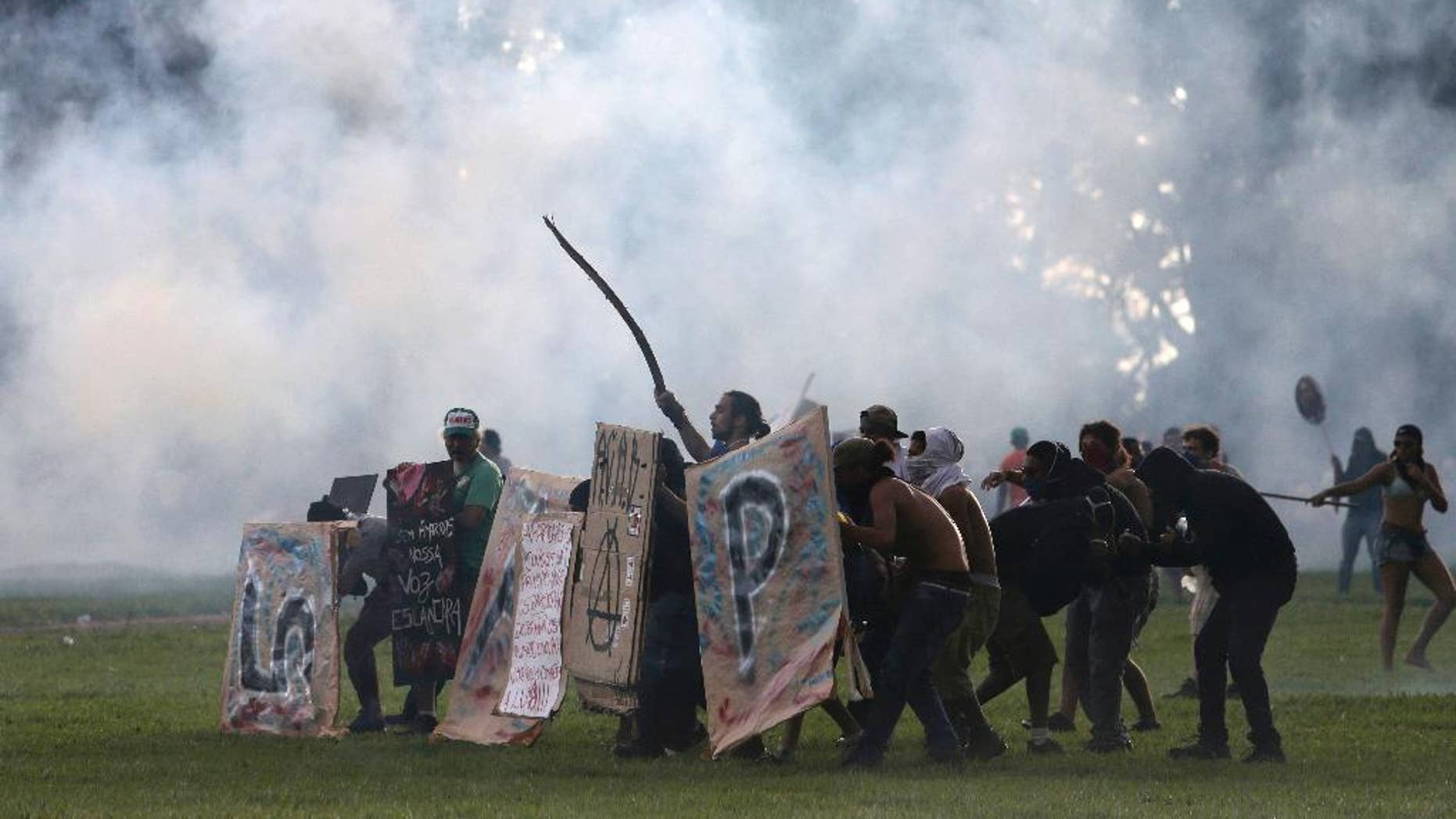 Protesters shield themselves as police fire tear gas outside Congress, where senators planned to vote on a spending cap bill and the lower Chamber of Deputies was considering controversial anti-corruption legislation, in Brasilia, Brazil, Tuesday, Nov. 29, 2016. Brazil, home to Latin America's largest economy, is suffering its worst recession in decades. (AP Photo/Eraldo Peres)