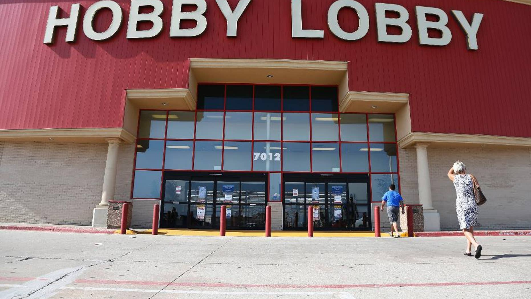 Customers walk to a Hobby Lobby store in Oklahoma City, Monday, June 30, 2014. The Supreme Court ruled Monday that employers can hold  religious objections that allow them to opt out of the new health law requirement that they cover contraceptives for women. The Hobby Lobby chain of arts-and-crafts stores is by far the largest employer of any company that has gone to court to fight the birth control provision. (AP Photo/Sue Ogrocki)