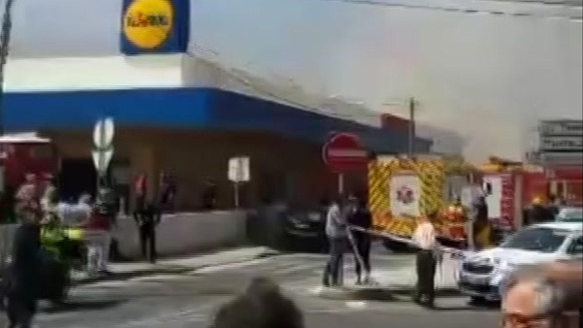 Smoke rises behind a supermarket near Lisbon after a small plane crashed. Portuguese officials say a small plane has crashed beside a supermarket near Lisbon, killing four people on board the aircraft and one on the ground. Four people were slightly injured. (Ramiro Ribeiro via AP)