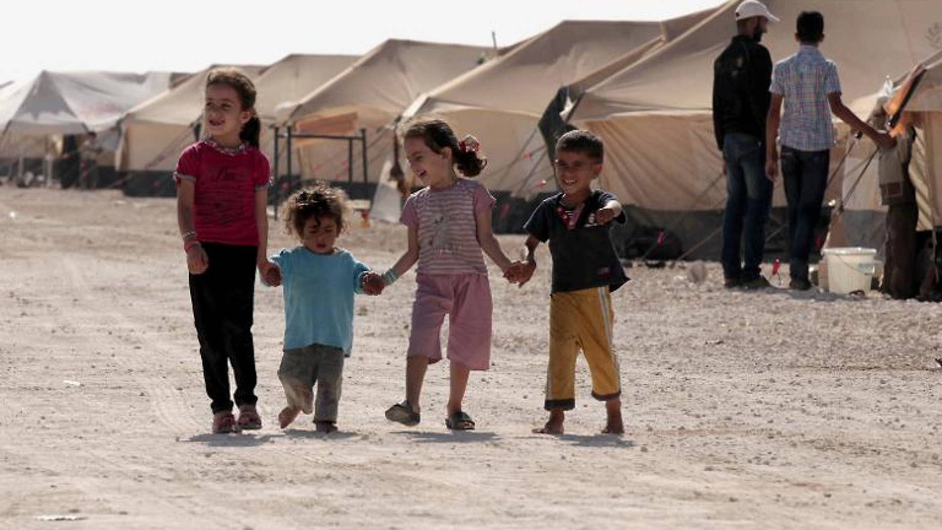 Syrian refugee children walk amid tents at the Zaatri refugee camp, near the Jordanian border with Syria, on September 11, 2012