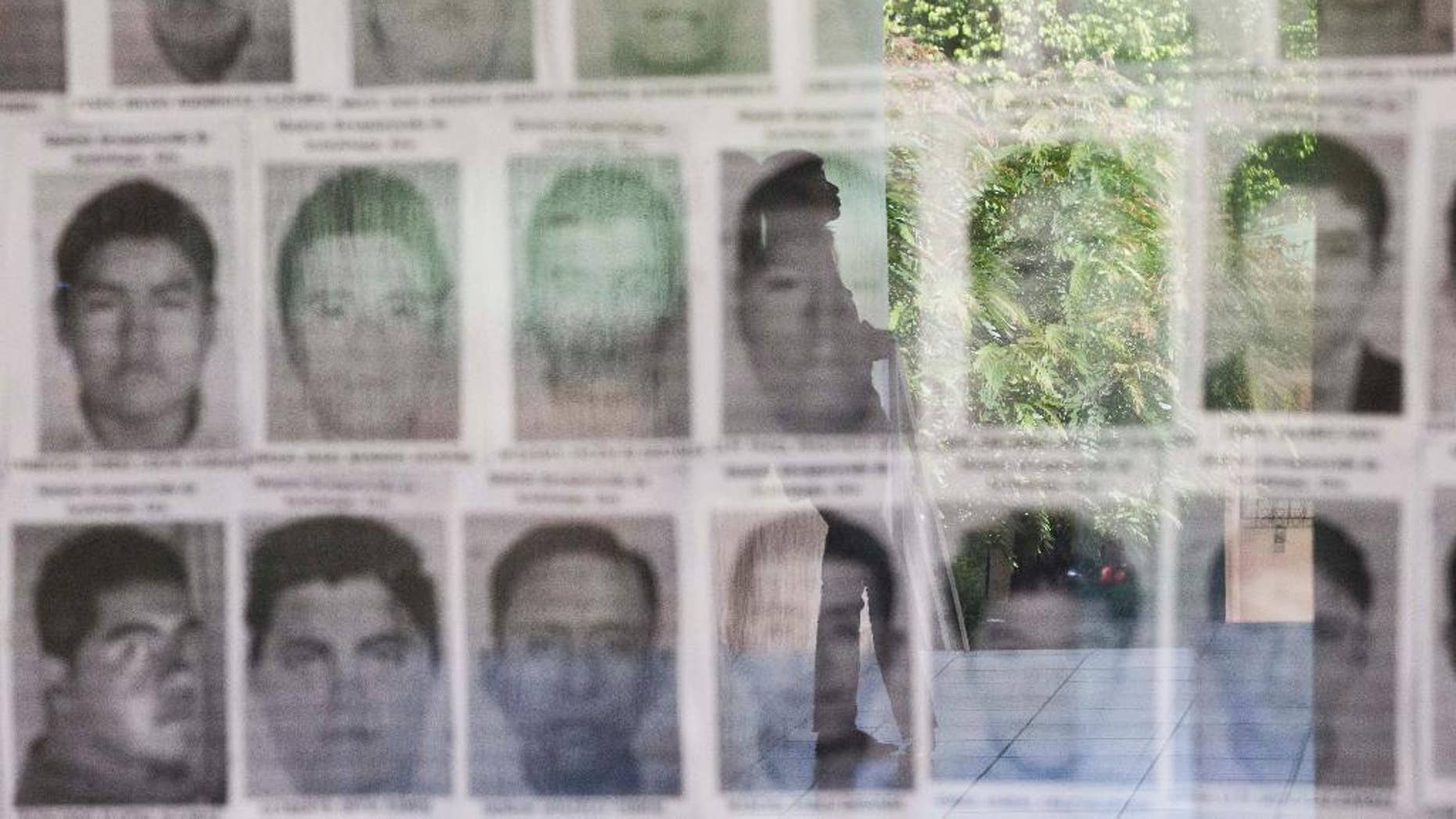 FILE - In this Nov. 18, 2014 file photo, a university student is reflected in a glass display case showing the photos of 43 missing students from the Rural Normal School of Ayotzinapa, Mexico, at the Central American University, UCA, in Managua, Nicaragua. Mexican authorities announced they detained on Friday, Oct. 21, 2016 the former police chief of Iguala where the students disappeared on Sept. 26, 2014. The students were taken by police and have not been heard from since. (AP Photo/Esteban Felix, File)