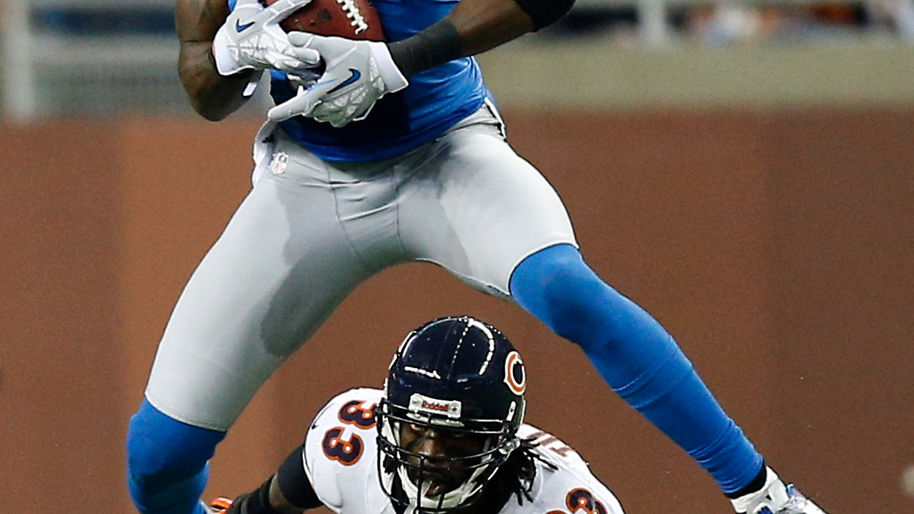 Detroit Lions wide receiver Calvin Johnson (81) gains 18-yards on a pass reception under pressure from Chicago Bears cornerback Charles Tillman (33) during the third quarter of an NFL football game at Ford Field in Detroit, Sunday, Dec. 30, 2012. (AP Photo/Rick Osentoski)