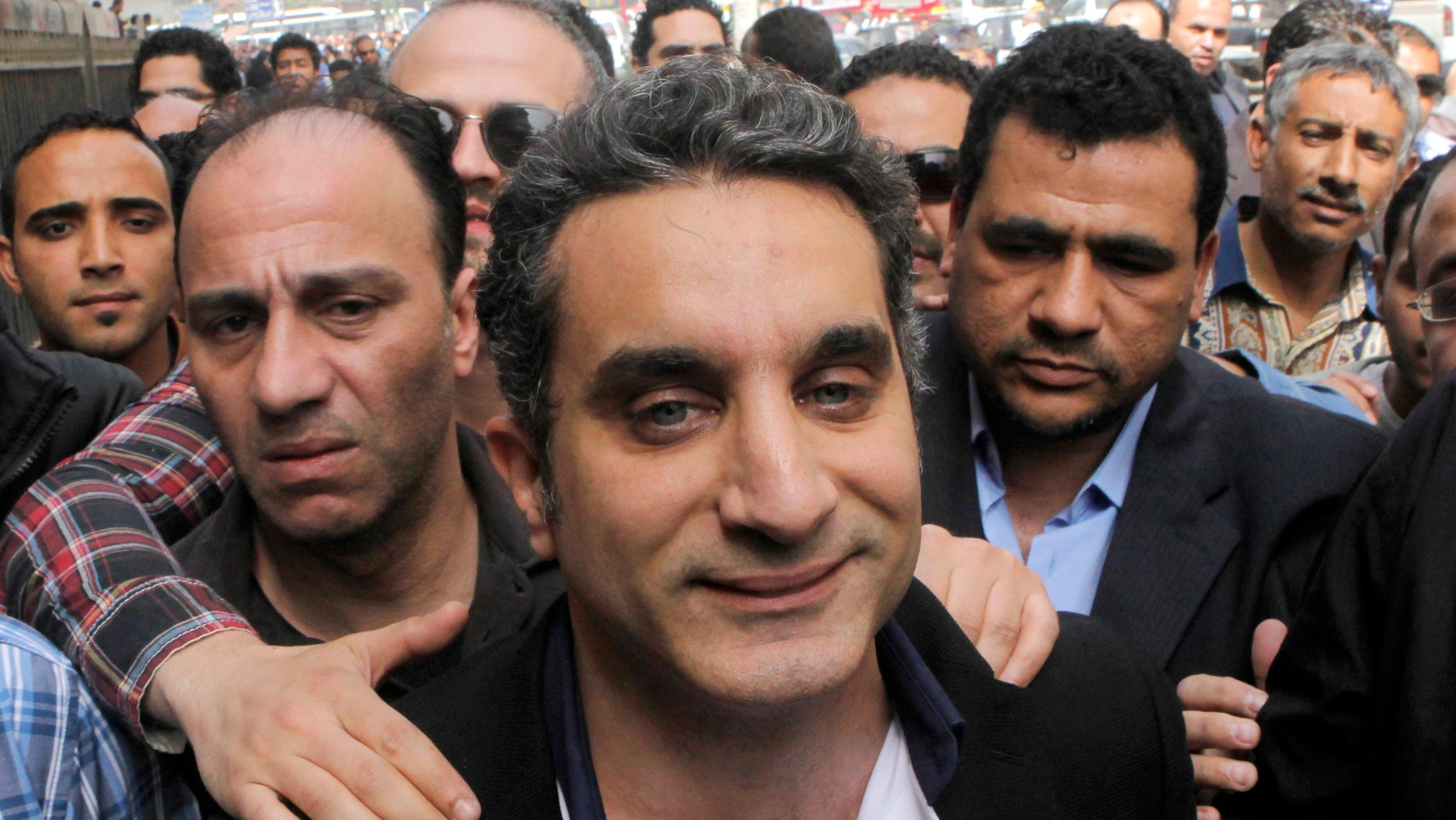 """FILE - In this Sunday, March 31, 2013 file photo, a bodyguard secures  popular Egyptian television satirist Bassem Youssef, who has come to be known as Egypt's Jon Stewart, as he enters Egypt's state prosecutors office to face accusations of insulting Islam and the country's Islamist leader in Cairo, Egypt. Egypt's state Investment Authority said Tuesday, April 2, 2013 it will revoke the license of a private TV station that airs a popular satirist if he does not stop the use of """"unacceptable and offensive"""" language. The warning comes two days after the satirist, Youssef, was questioned by prosecutors over accusations that he insulted Islamist President Mohammed Morsi and Islam, and a day after the U.S. criticized the Egyptian government for a """"disturbing trend"""" of growing restrictions on freedom of expression. (AP Photo/Amr Nabil, File)"""