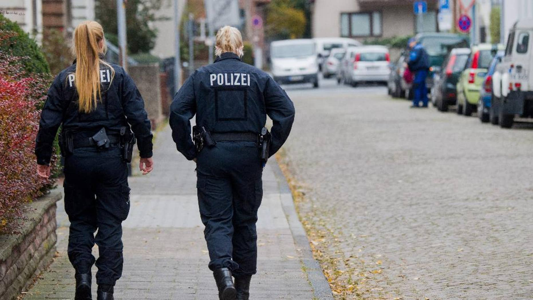 Policewomen  walk along  a street in Hameln, Germany, Monday Nov. 21, 2016. A woman was seriously injured when she was dragged Sunday through the streets of the northern German town behind a car with a cord tied around her neck. Her ex-partner later turned himself in to authorities, prosecutors said Monday,  (Julian Stratenschulte/dpa via AP)