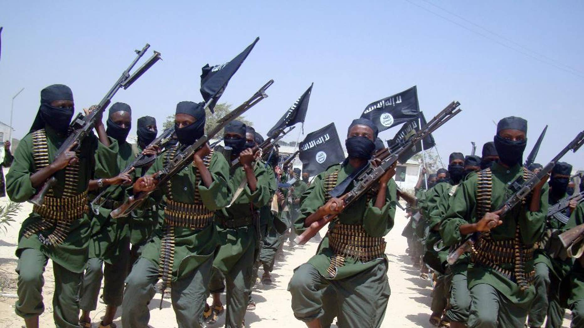 FILE - In this Thursday, Feb. 17, 2011 file photo, al-Shabab fighters march with their weapons during military exercises on the outskirts of Mogadishu, Somalia.  A U.S. drone strike in Somalia has targeted a key leader of the al-Shabab militant group who was involved in two attacks in Mogadishu more than a year ago that killed more than 30 people, at least three Americans among them, the Pentagon said Friday, April 1, 2016. Several U.S. officials said he and two others were killed. Hassan Ali Dhoore was targeted in the airstrike Thursday, but the U.S. military was still assessing the results, Pentagon spokesman Peter Cook said in a statement. (AP Photo/Mohamed Sheikh Nor, File)