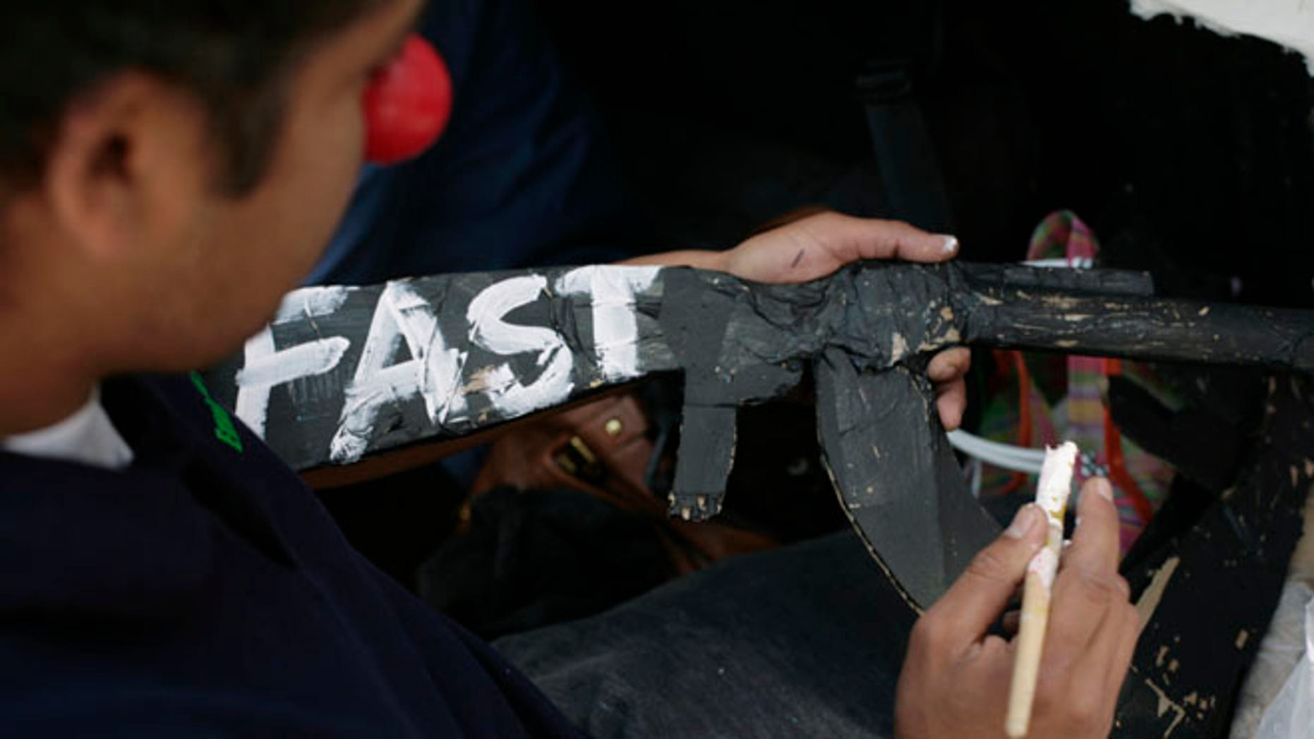 """FILE: October 14, 2011: A man writes """"Fast"""" -- in reference to Operation Fast and Furious -- on a paper mache gun during a protest in Mexico City ."""
