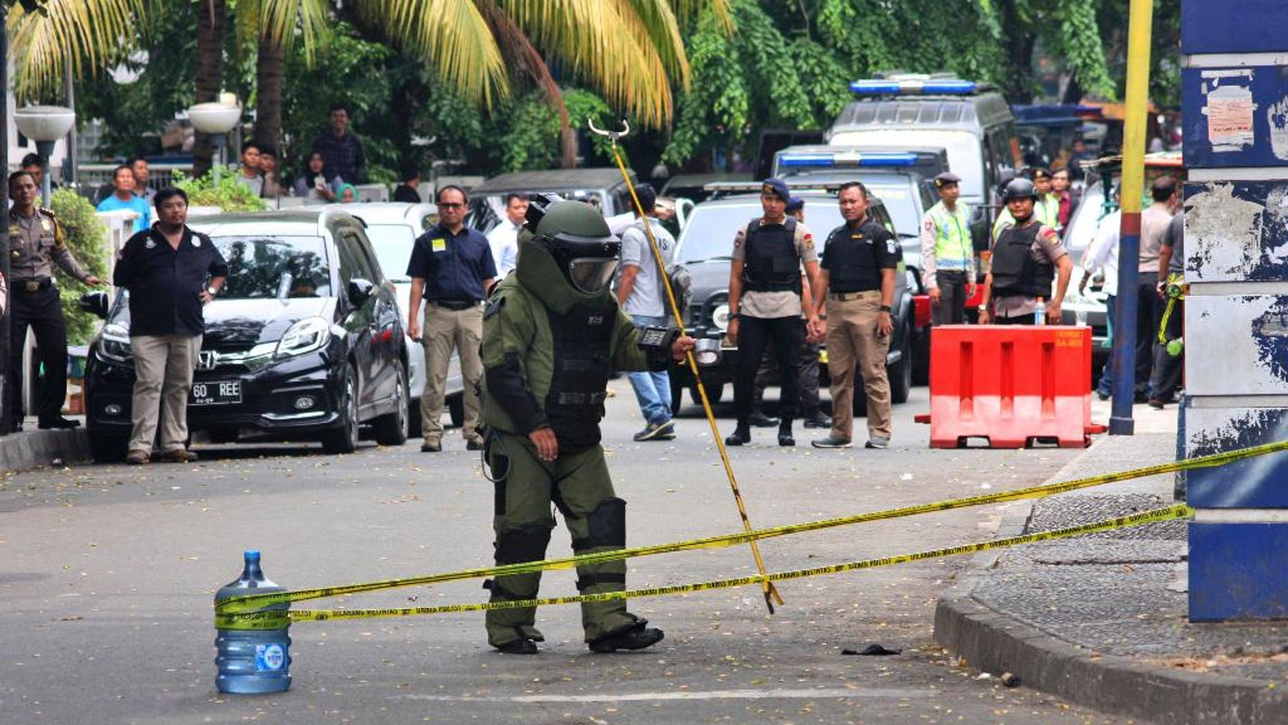 A member of police bomb squad inspects the site where police officers were attacked earlier, in Tangerang, Indonesia, Thursday, Oct. 20, 2016. A man with an Islamic State group symbol was shot Thursday after attacking the officers with a machete, police said. (AP Photo)
