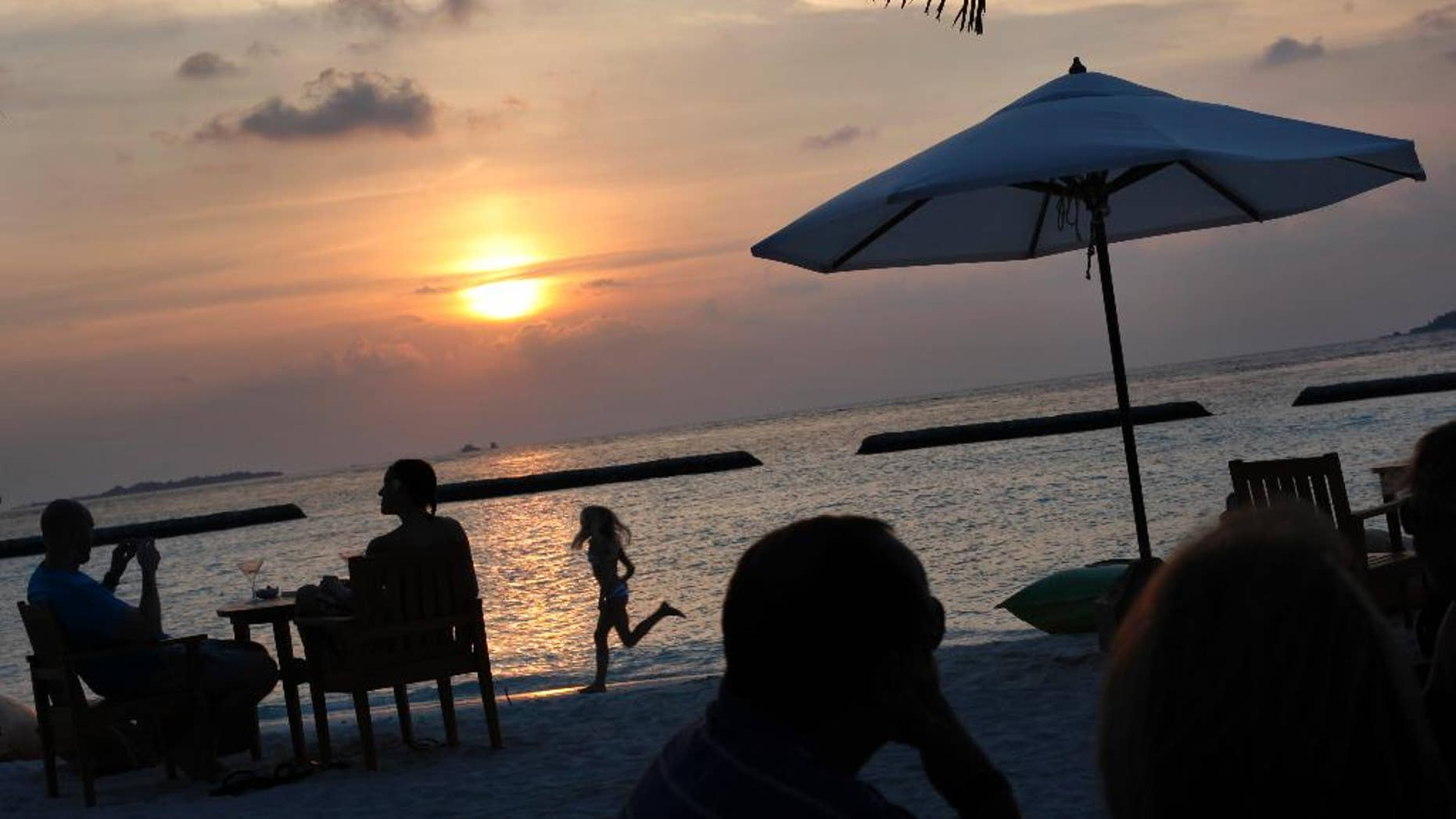 FILE - In this Feb. 16, 2012, file photo, foreign tourists gather at a sand-bar to watch sunset at Kurumba resort in Male atoll, Maldives. Maldives, best known for its palm-fringed beaches and luxury resorts, but riven by political power struggles since becoming a democracy only seven years ago. An explosion in September 2015 aboard the presidential boat set the Maldives on course for its latest political shakeup, with the Vice President Ahmed Adeeb arrested over the weekend on suspicion of high treason for allegedly plotting to assassinate the country's leader. (AP Photo/Gemunu Amarasinghe, File)