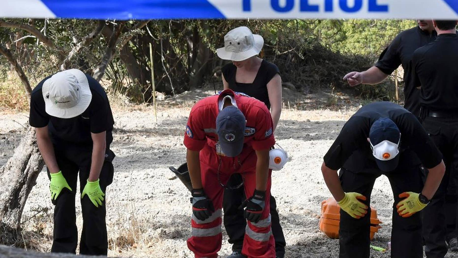 FILE - In this Monday, Sept. 26, 2016 file photo, British officers and members of the Greek rescue team search an area of land on the southeastern Greek island of Kos. A British toddler who went missing on a Greek island 25 years ago is believed to have been killed in a construction-site accident that was covered up for almost a quarter of a century, police said Monday, Oct. 17, 2016. (Nikos Panagiotopoulos/InTime News via AP, file)