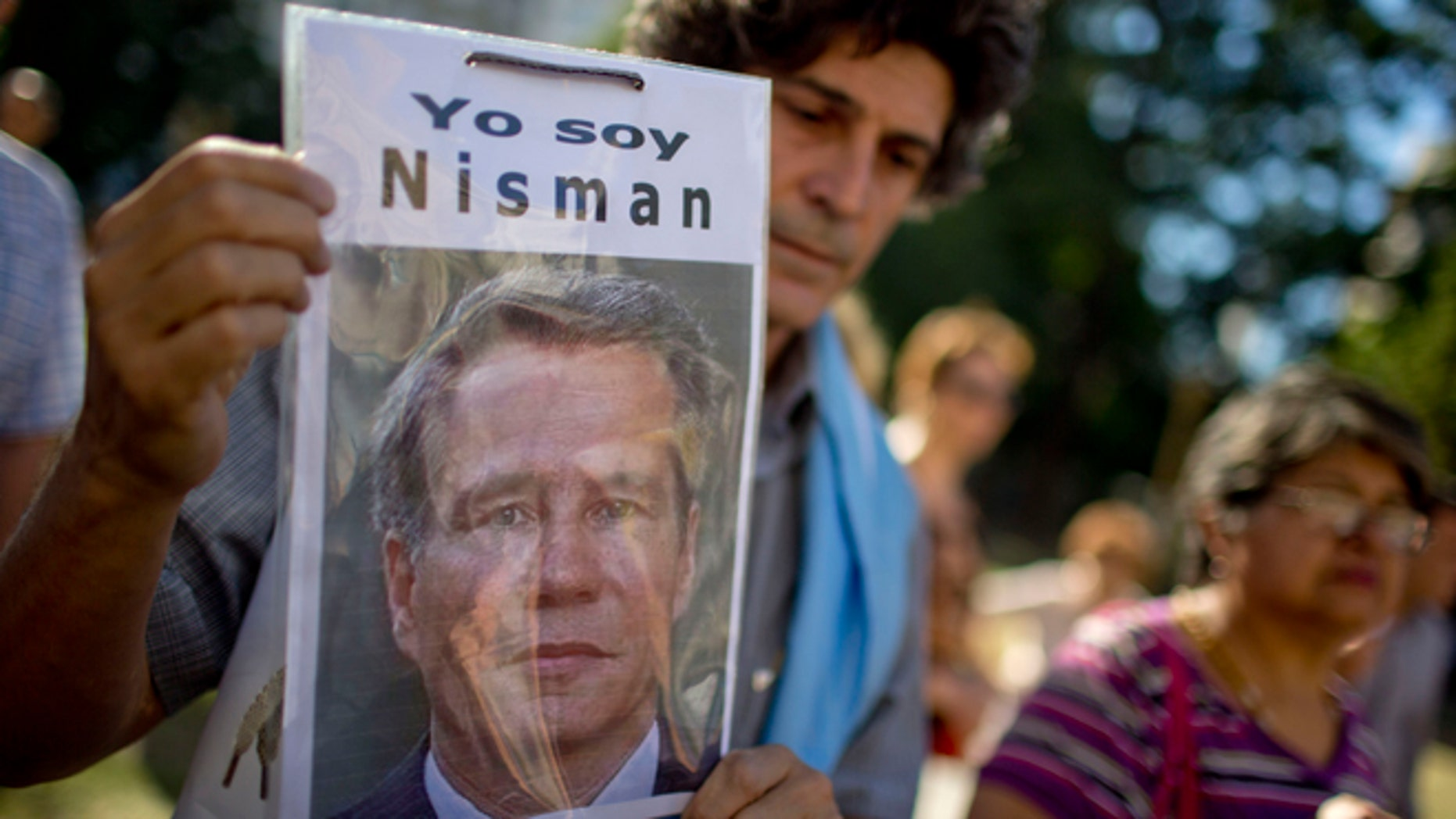 """A demonstrator holds a photo of late prosecutor Alberto Nisman that reads in Spanish """"I am Nisman"""" during an protest to demand justice after more than one month since his death outside a court house in Buenos Aires, Argentina, Wednesday, March 18, 2015. Nisman was found dead in his bathroom on January 18, on the eve of congressional hearings where he was due to present his accusations against President Cristina Fernandez of shielding Iranian officials from prosecution over the 1994 bombing of a Buenos Aires Jewish center. (AP Photo/Natacha Pisarenko)"""