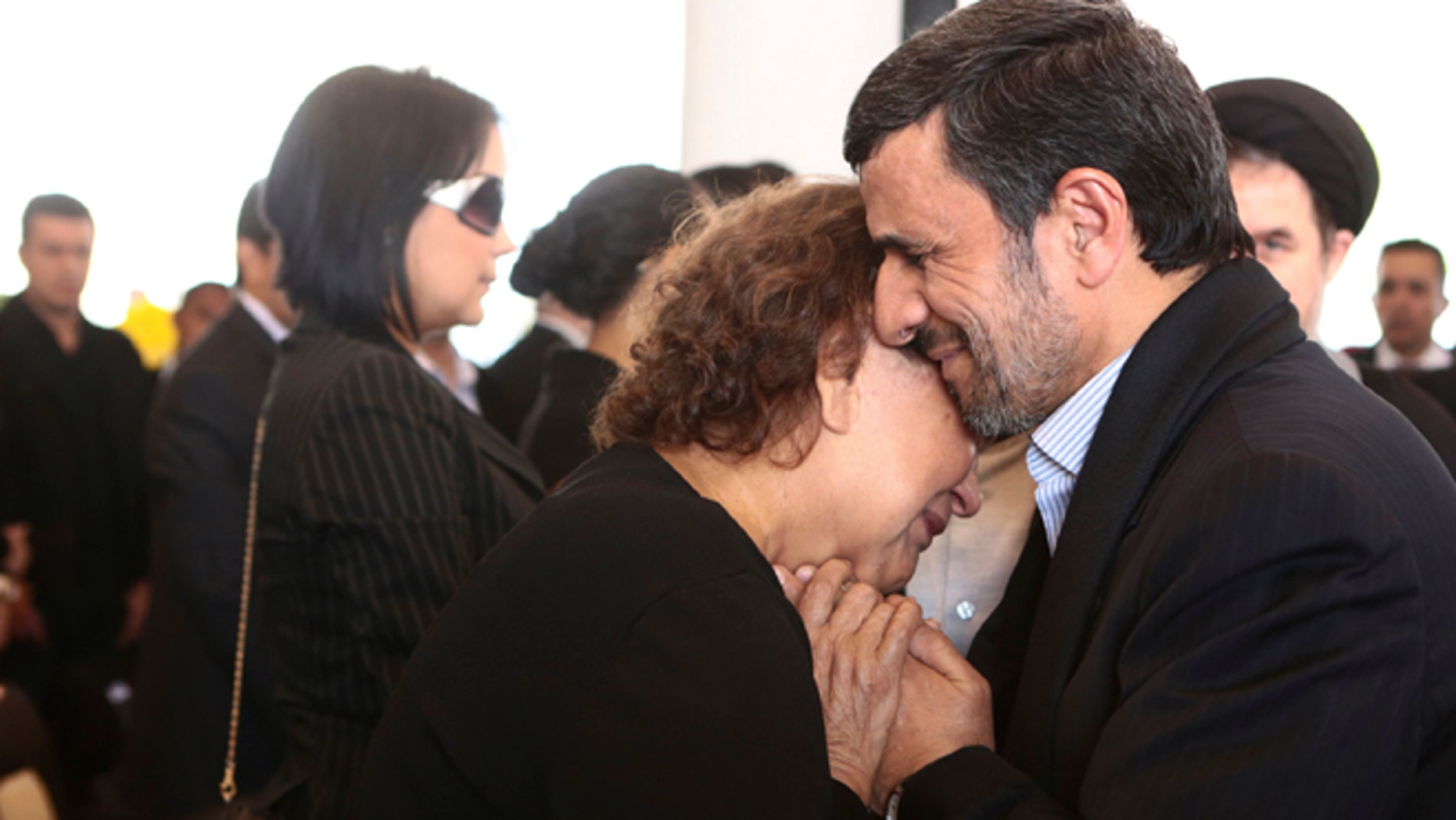 FILE --In this Friday, March 8, 2013 file photo released by the Miraflores Press Office, Iran's President Mahmoud Ahmadinejad comforts Elena Frias next to the flag-draped coffin of her son, Venezuela's late President Hugo Chavez, during the funeral ceremony at the military academy in Caracas, Venezuela.