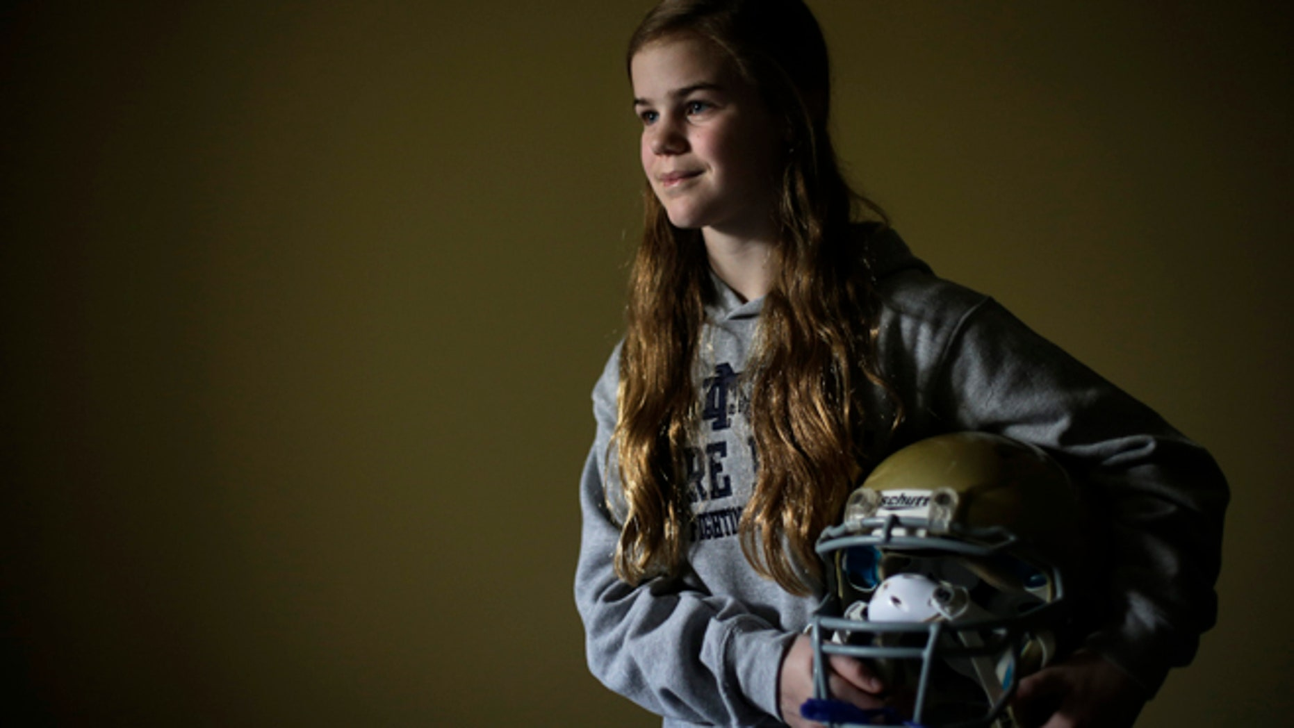 This photo taken Feb. 21, 2013, shows Caroline Pla, 11, posing for a photo with her helmet in Doylestown, Pa.