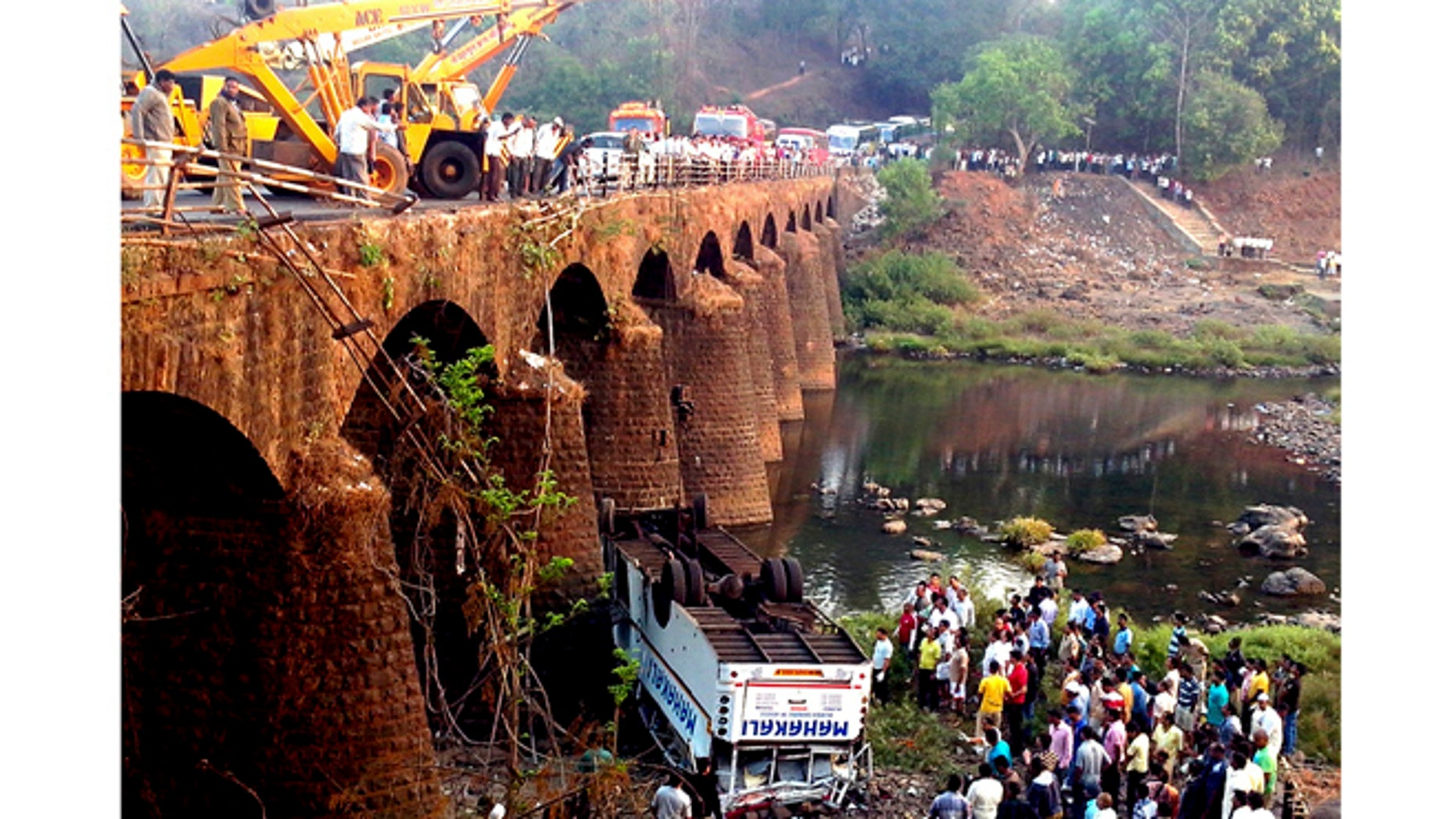 March 19, 2013: Rescuers and others gather at the site of a bus accident in Ratnagiri district, in the western Indian state of Maharashtra.