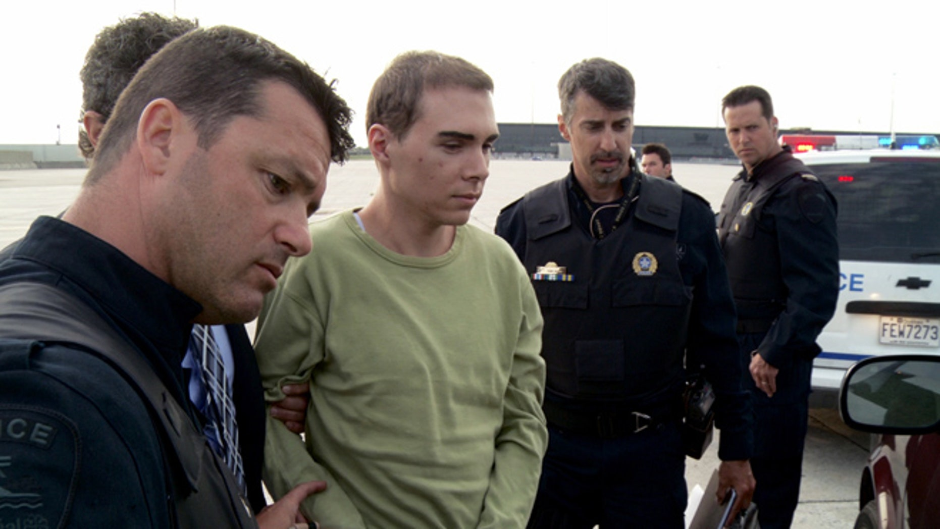 June 18, 2012: In this file photo provided by Montreal Police, Luka Rocco Magnotta is taken by police from a Canadian military plane to a waiting van in Mirabel, Quebec.