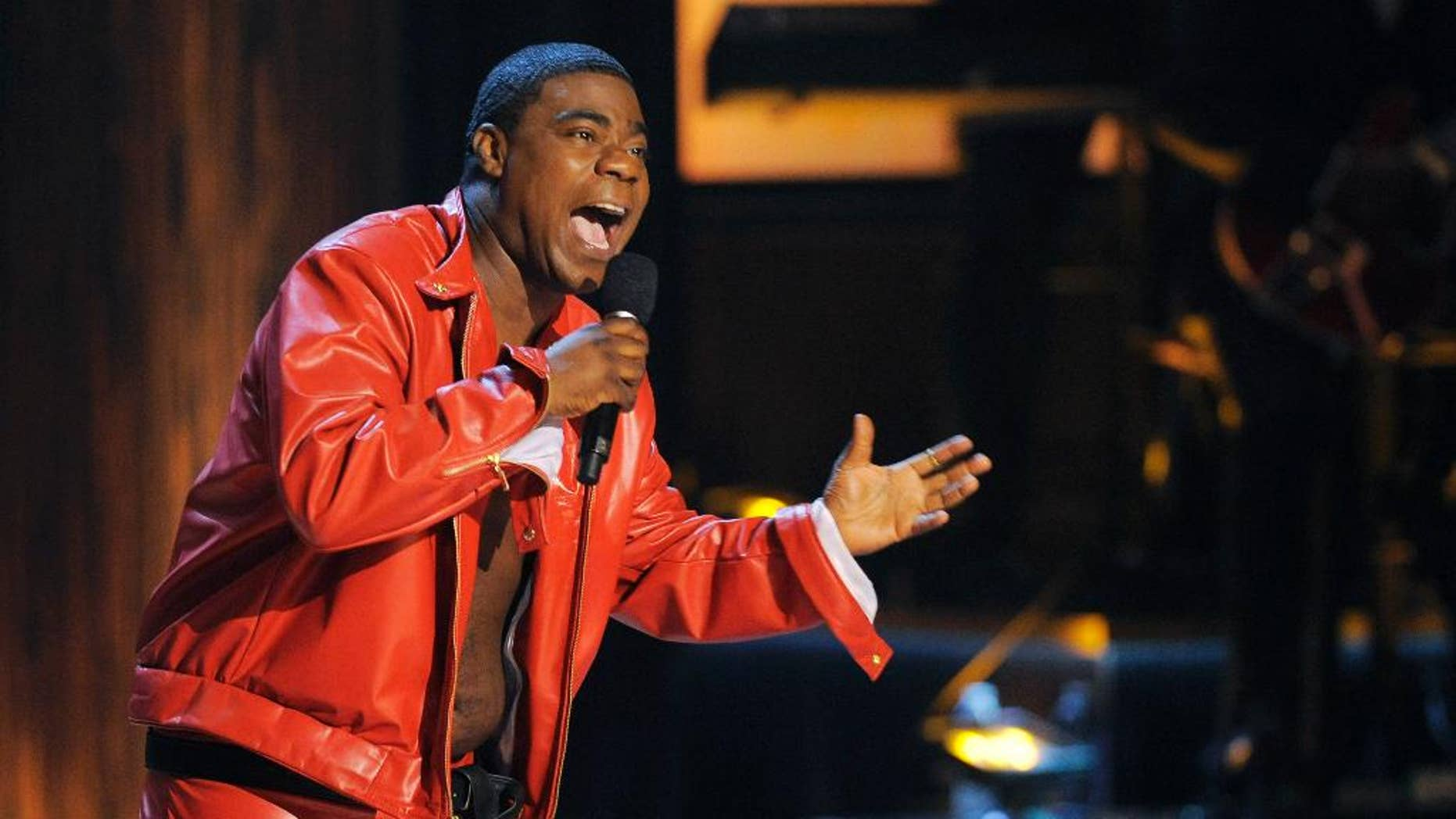 "FILE - In this Nov. 3, 2012 file photo, comedian Tracy Morgan performs at ""Eddie Murphy: One Night Only,"" a celebration of Murphy's career at the Saban Theater in Beverly Hills, Calif. Morgan is recovering but is expected to remain hospitalized for several weeks after having surgery on a broken leg suffered in a chain-reaction crash on the New Jersey Turnpike early Saturday, June 7, 2014, that left two others critically injured and one dead. (Photo by Chris Pizzello/Invision, File)"