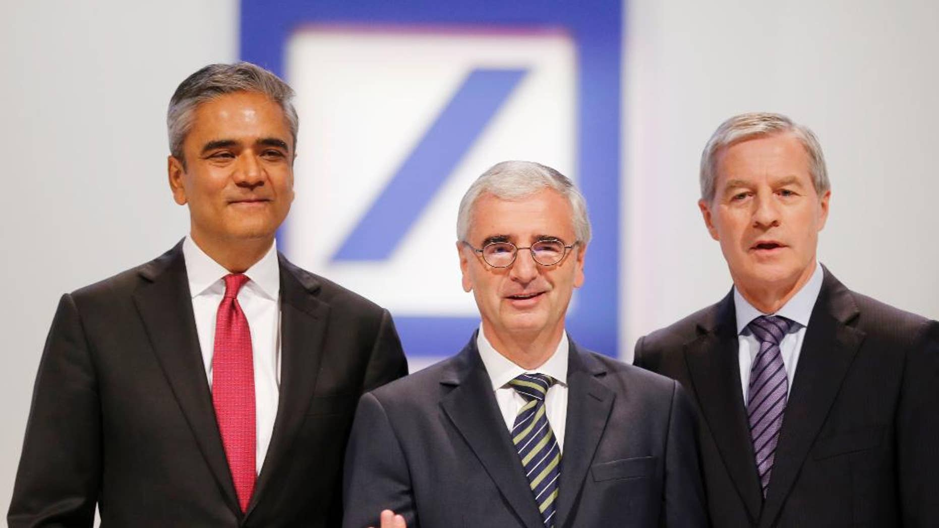 FILE - In this May 22, 2014 file photo Co-CEOs of Deutsche Bank Anshu Jain, left, and Juergen Fitschen, right, and the head of supervisory board Paul Achleitner pose for photographers at the beginning of the annual shareholders meeting in Frankfurt, Germany. Deutsche Bank said Sunday, June 7, 2015 that Jain and Fitschen will resign.  John Cryan will succeed Jain in July 2015 and will become the sole CEO in May 2016.  (AP Photo/Michael Probst, file)