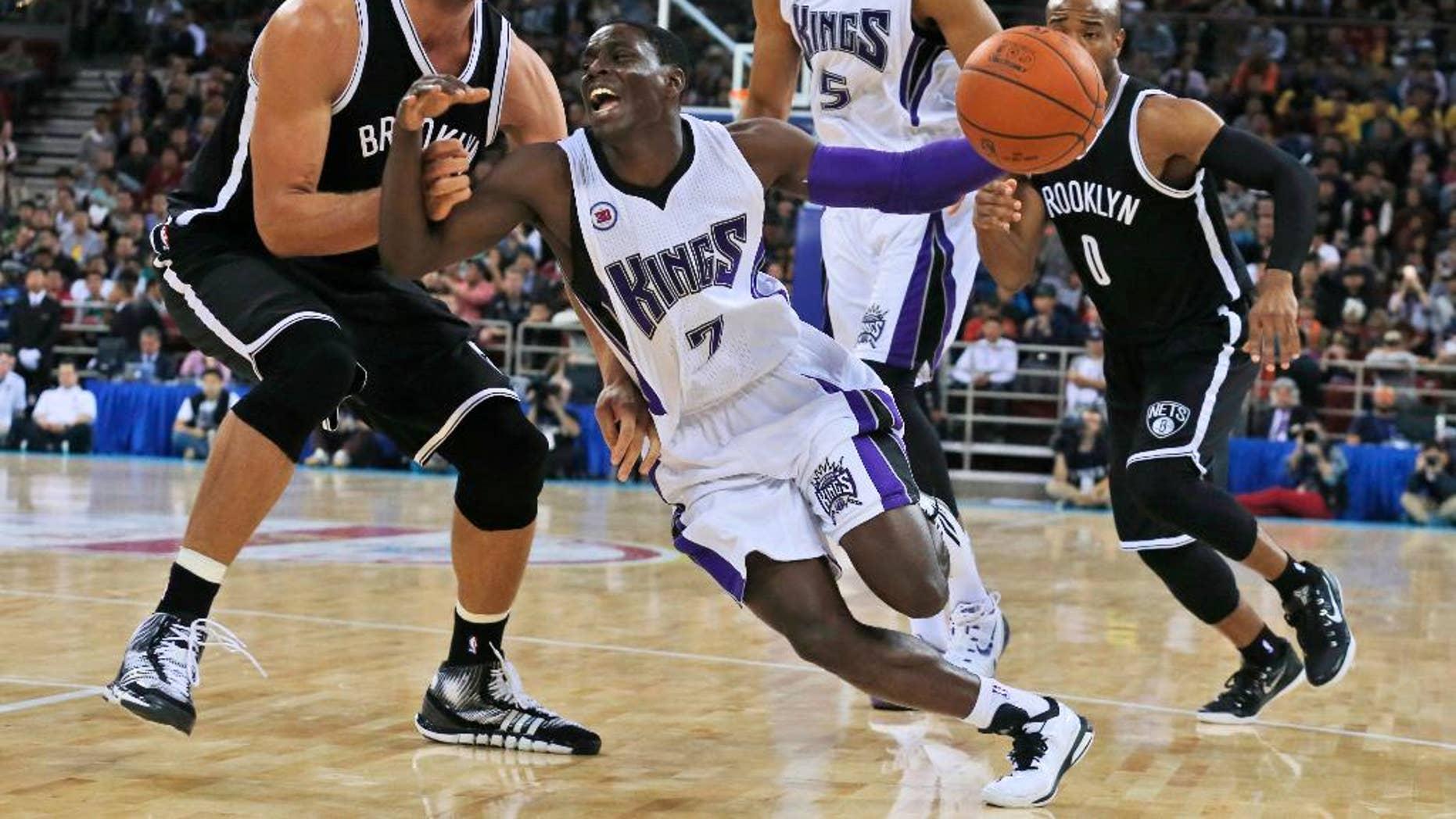 Sacramento Kings' Darren Collison, center, tries to pass Brooklyn Nets' Brook Lopez, left, during a pre-season match held in Beijing, China, Wednesday, Oct. 15, 2014. Brooklyn Nets won 129-117. (AP Photo/Ng Han Guan)