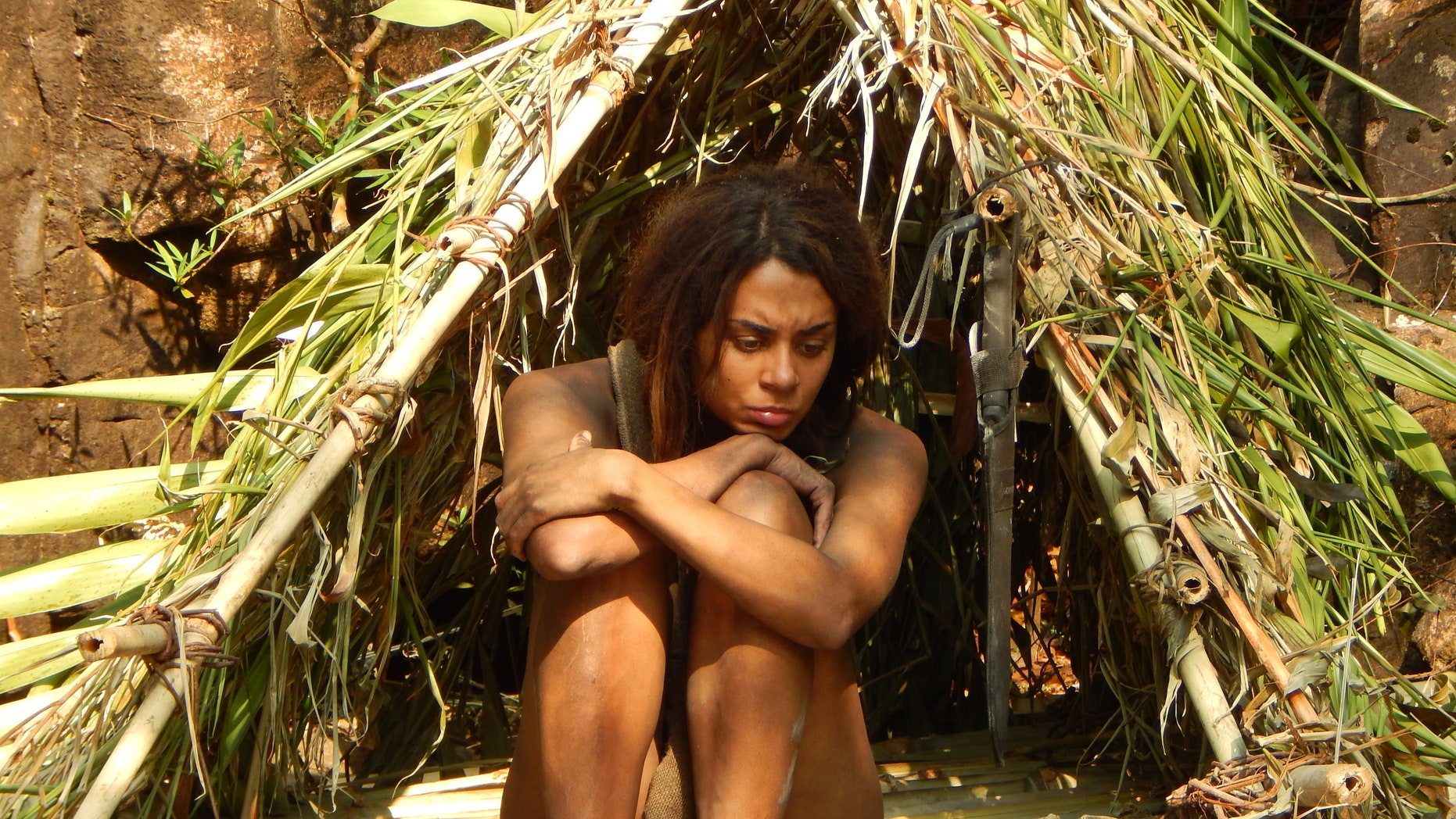 """Carrie sitting in her and Tom's shelter as she waits out the 21 days of survival to be over on """"Naked and Afraid."""""""