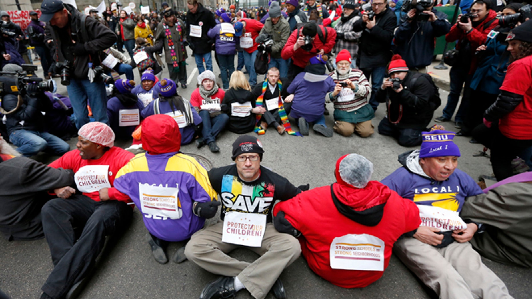 March 27, 2013: Protesters sit on LaSalle Street during an act of civil disobedience over a plan to close 54 Chicago Public Schools in  Chicago's downtown.