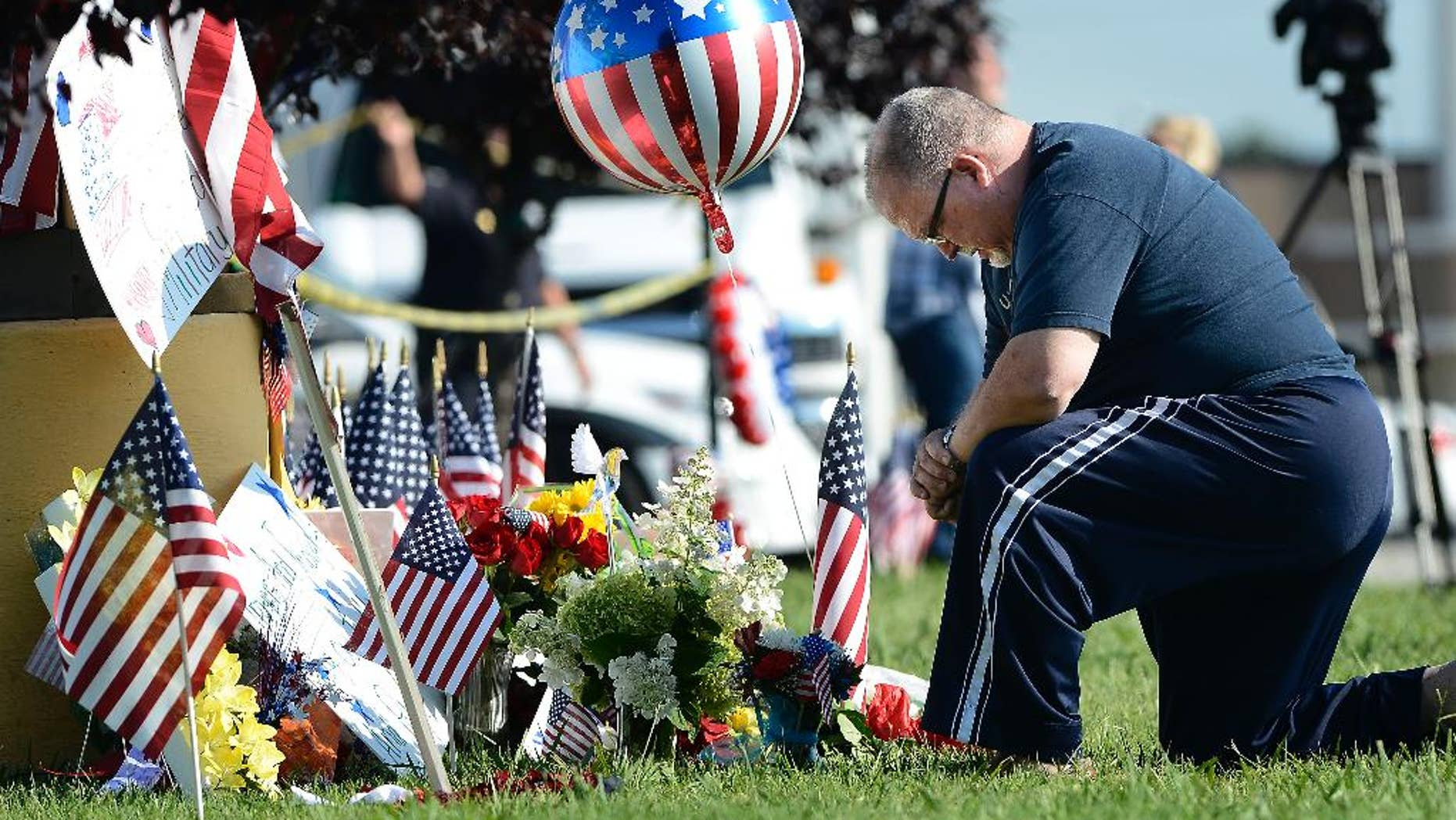 Bill Lettmkuhl kneels by a makeshift memorial in front of near the Armed Forces Career Center on Friday, July 17, 2015, in Chattanooga, Tenn. Muhammad Youssef Abdulazeez, of Hixson, Tenn., attacked two military facilities on Thursday, in a shooting rampage that killed four Marines. (AP Photo/Mark Zaleski)