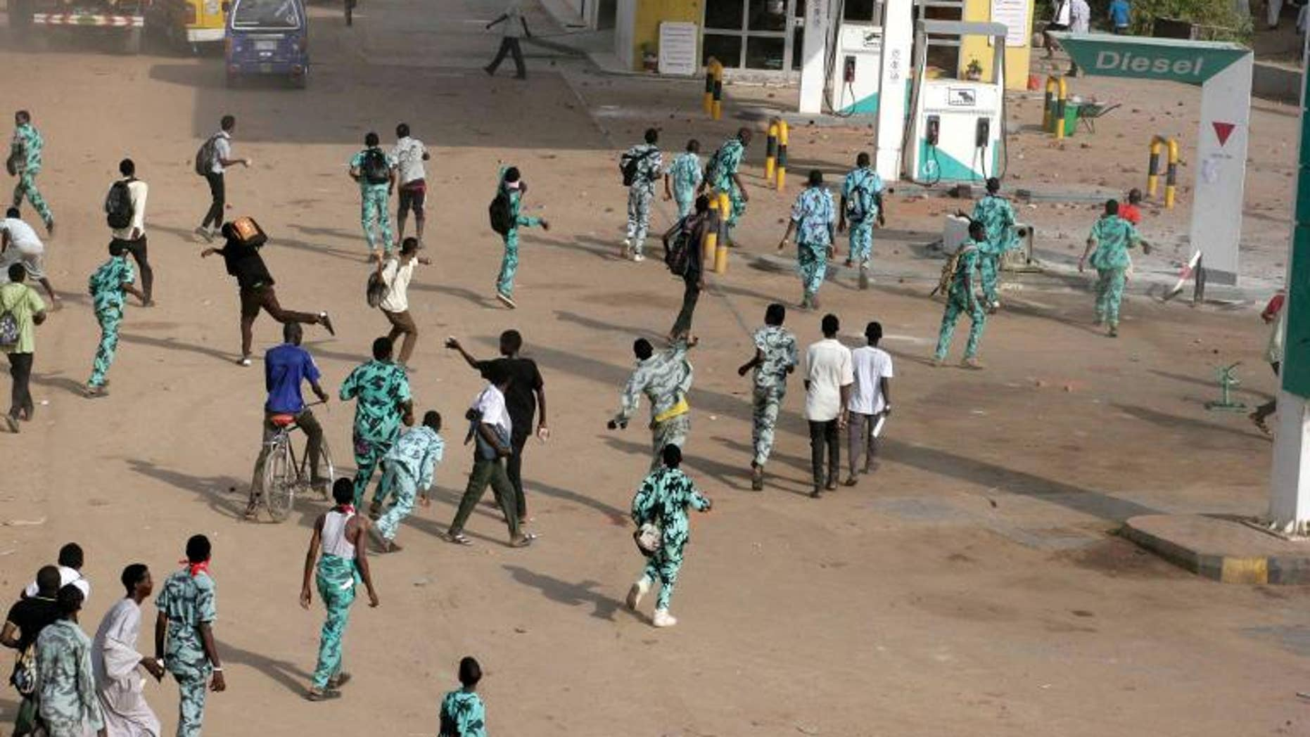 Sudanese protestors throw stones at a petrol station in Khartoum's twin city of Omdurman during a demonstration after the government announced steep price rises for petroleum products on September 25, 2013