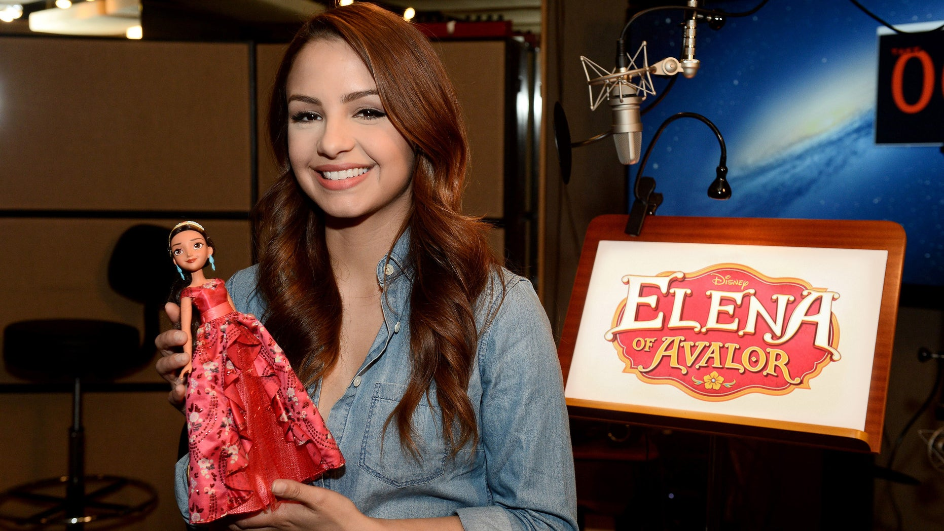 """Actress Aimee Carrero, who voices the title role in Disney's """"Elena of Avalor,"""" gets a first-look at the new Elena doll during a recording session for the series in Burbank, California.  The doll, from Hasbro, will debut at Toy Fair in New York City on Friday, February 12, and """"Elena of Avalor,"""" a new animated TV series set in a fairytale kingdom inspired by Latin cultures and folklore, will premiere this summer on Disney Channel. (Disney Junior/Matt Petit)AIMEE CARRERO"""