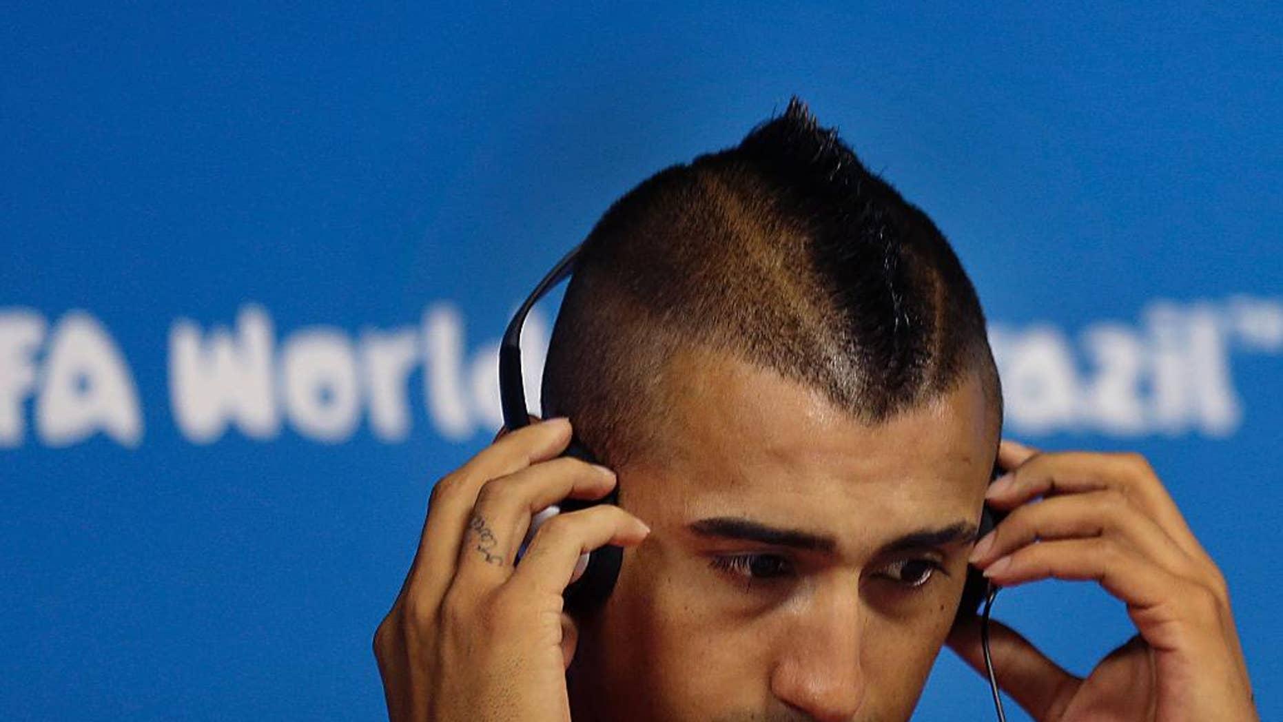 El jugador de Chile, Arturo Vidal, se ajusta los audífonos en una conferencia de prensa el domingo, 22 de junio de 2014, en Sao Paulo, Brasil.  (AP Photo/Wong Maye-E)