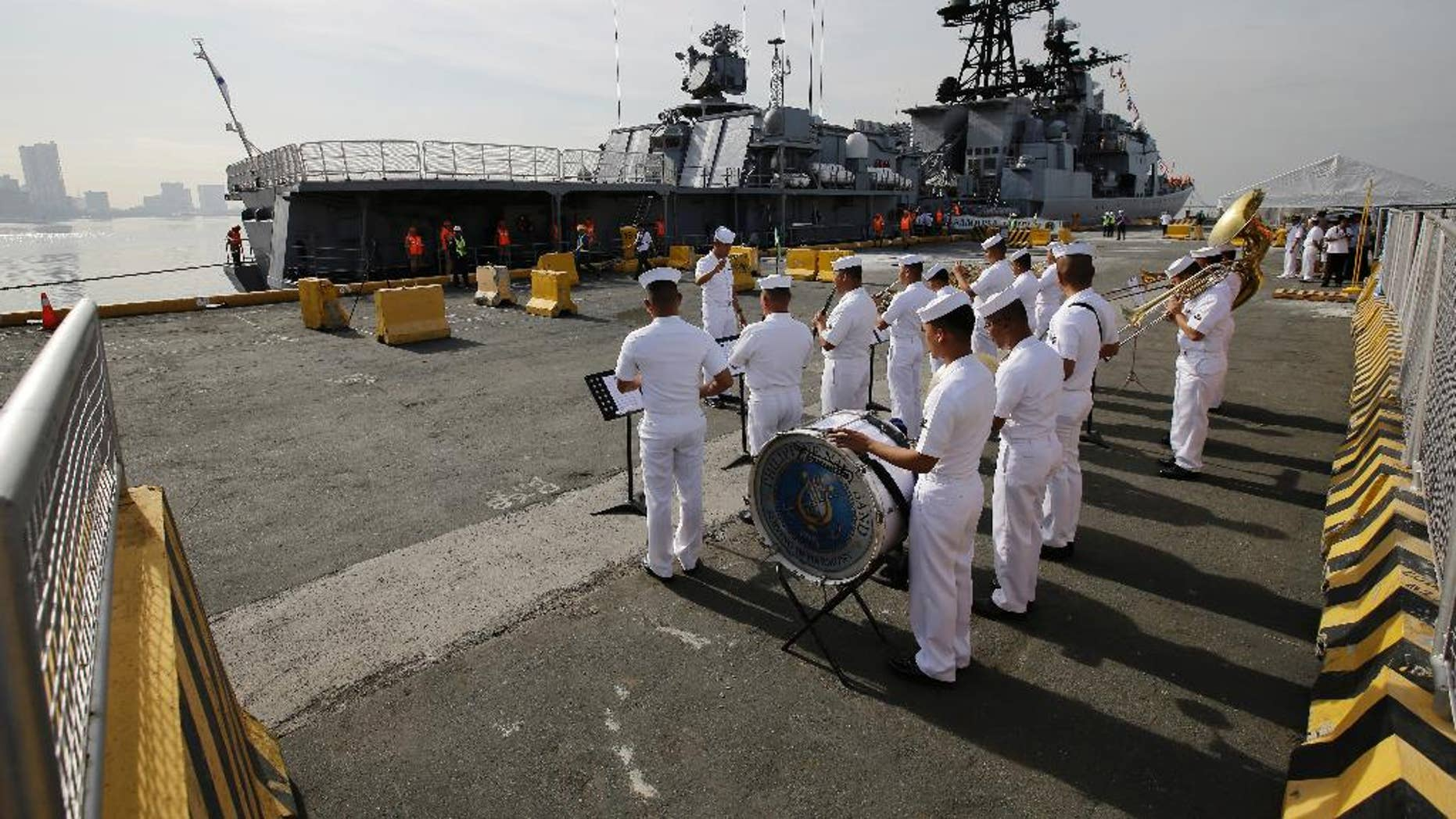 A Philippines Navy Band plays as the Russian Navy vessel Admiral Tributs, a large anti-submarine ship, docks at Manila's pier on Tuesday.