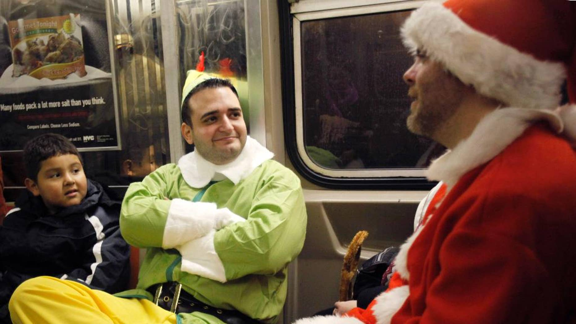 FILE - In this Dec. 11, 2010, file photo, John Paul, center, dressed as an Elf and Michael Smallwood, in a Santa Claus outfit, ride the E train in New York. Paul and Smallwood were participants in SantaCon, an annual holiday pub crawl during which participants dress up as Santa Claus or wear Christmas-themed clothing. As thousands of Santa-suited merrymakers prepare to hit the city's streets and bars Saturday, Dec. 12, 2015, organizers say they're taking steps to deter naughty behavior. (AP Photo/Mary Altaffer, File)