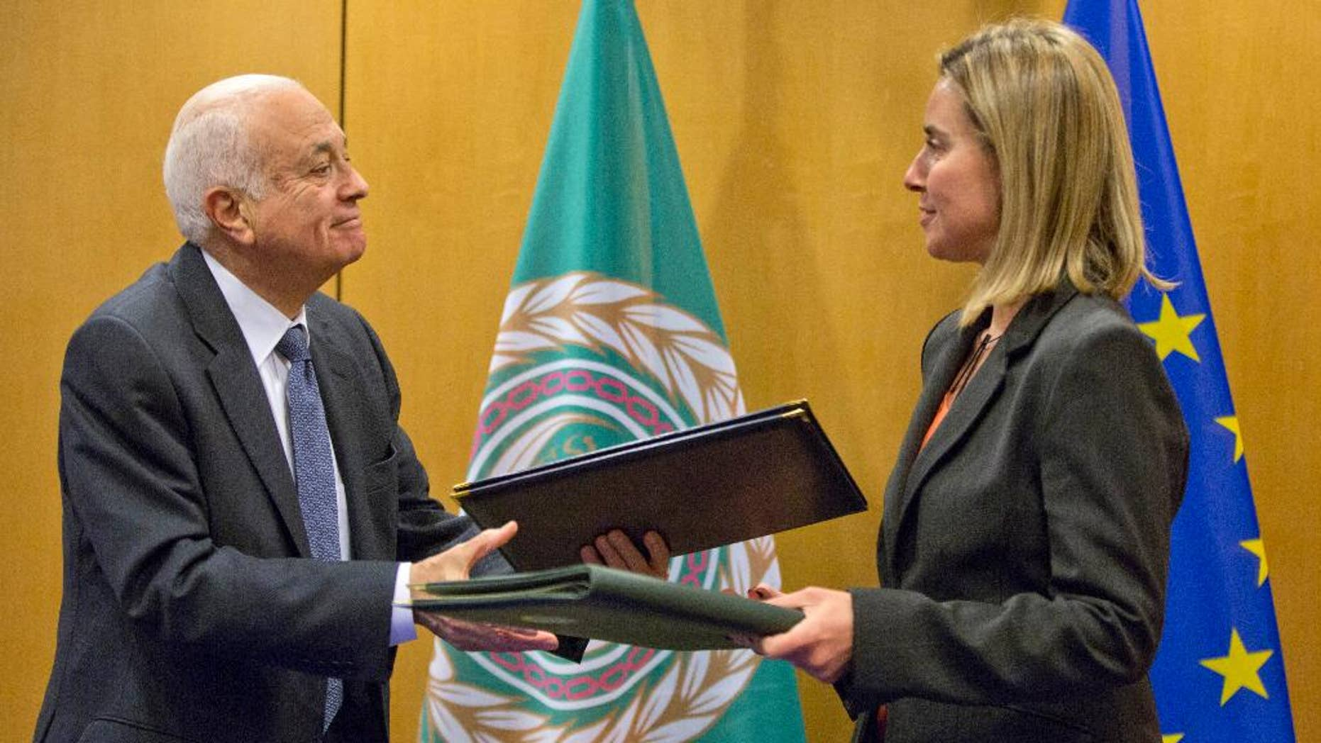 Secretary General of the Arab League Nabil Al-Araby, left, exchanges booklets with European Union High Representative Federica Mogherini after signing a cooperation agreement after a meeting of EU foreign ministers in Brussels on Monday, Jan. 19, 2015. The European Union is calling for an anti-terror alliance with Arab countries to boost cooperation and information sharing in the wake of deadly attacks and arrests across Europe linked to foreign fighters. (AP Photo/Virginia Mayo)