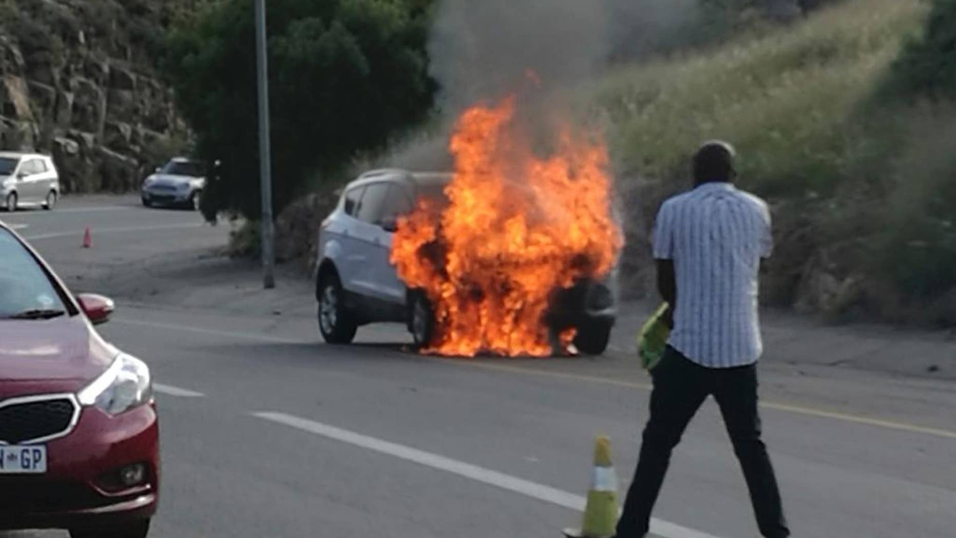 In this photo taken Thursday, Jan. 12, 2017 the 2013 Ford Kuga owned by Warren Krog burns out in Alberton JohannesburgThe South African unit of the Ford Motor Company says it is recalling 4,556 Kuga vehicles following several dozen reports of the car catching fire. Jeff Nemeth, Ford's regional chief executive, said Monday Jan. 16 2017, that 1.6-liter Kugas made between December 2012 and February 2014 must be taken to a Ford dealer as soon as possible. (AP Photo/Warren Krog)
