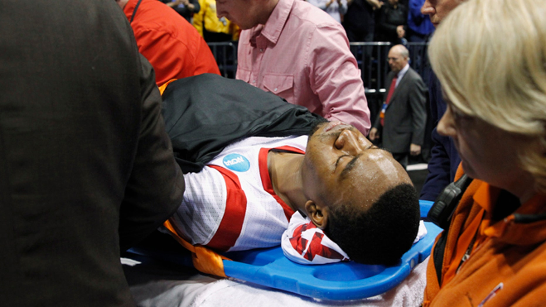 Louisville guard Kevin Ware is taken off of the court  on a stretcher after his injury during the first half of the Midwest Regional final against Duke in the NCAA college basketball tournament Sunday March 31, 2013, in Indianapolis. (AP Photo/Darron Cummings)