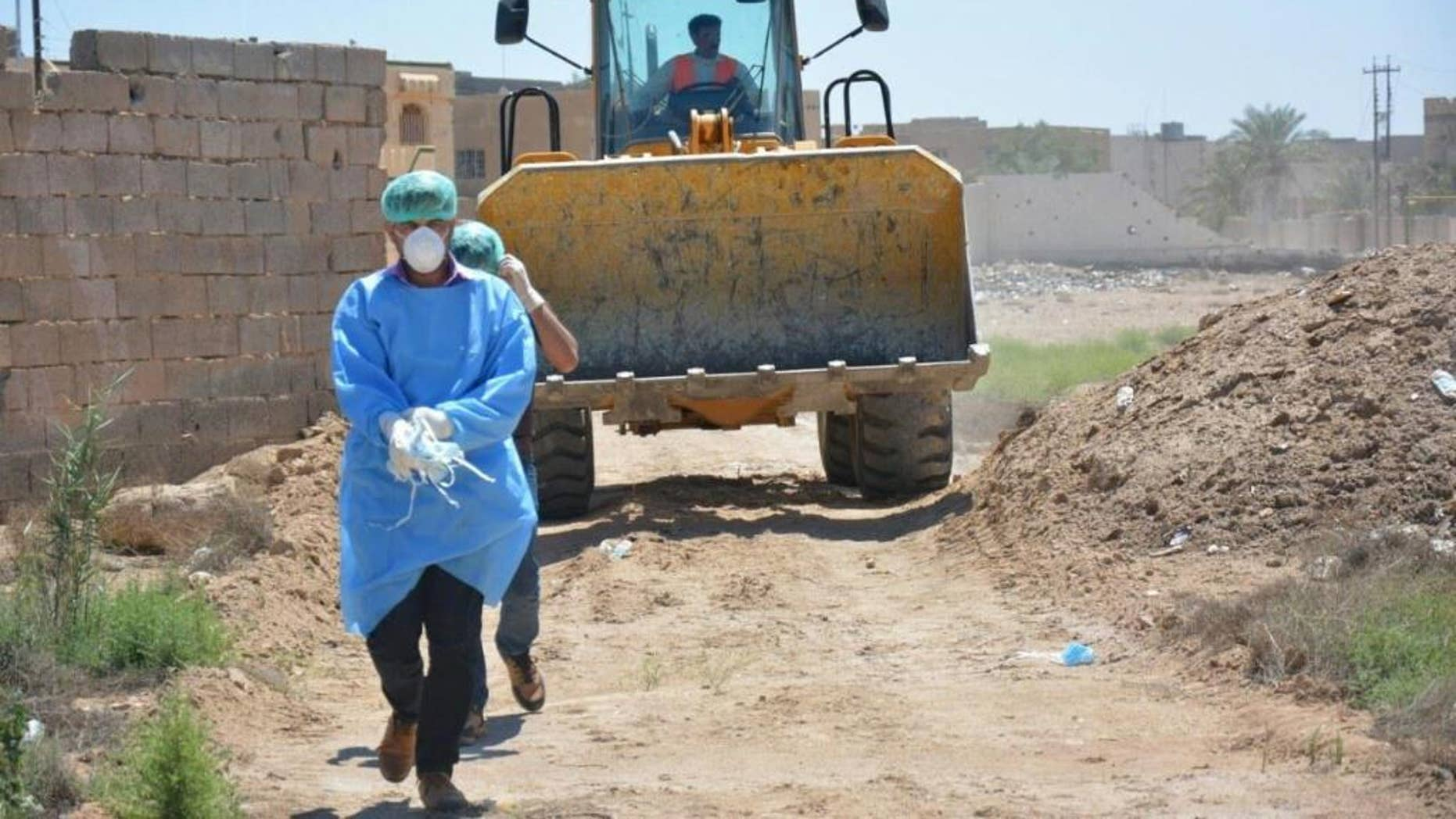 An Iraqi security forces forensic team works at at the site of a mass grave, one of two discovered containing the bodies of dozens of men, women and children killed by Islamic State group militants, in the stadium area in Ramadi, 115 kilometers (70 miles) west of Baghdad, Iraq, Tuesday, April 19, 2016. (AP Photo)