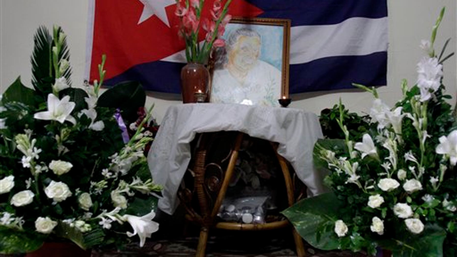 A painting of Laura Pollan, late leader of the dissident group Ladies in White, is flanked by flowers, candles and a Cuban flag during a gathering in her honor at her home in Havana, Cuba, Saturday Oct. 15, 2011.