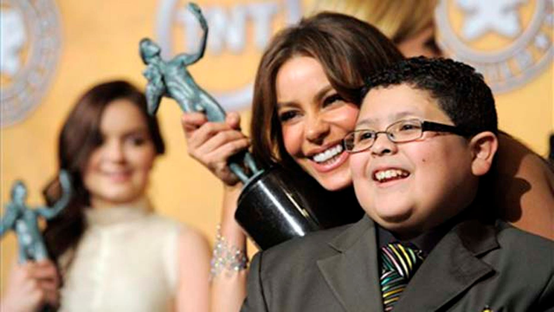 """As Ariel Winter looks on, left, Sofia Vergara and Rico Rodriguez pose together with their best comedy series trophies for """"Modern Family"""" at the 17th Annual Screen Actors Guild Awards on Sunday, Jan. 30, 2011 in Los Angeles. (AP Photo/Chris Pizzello)"""