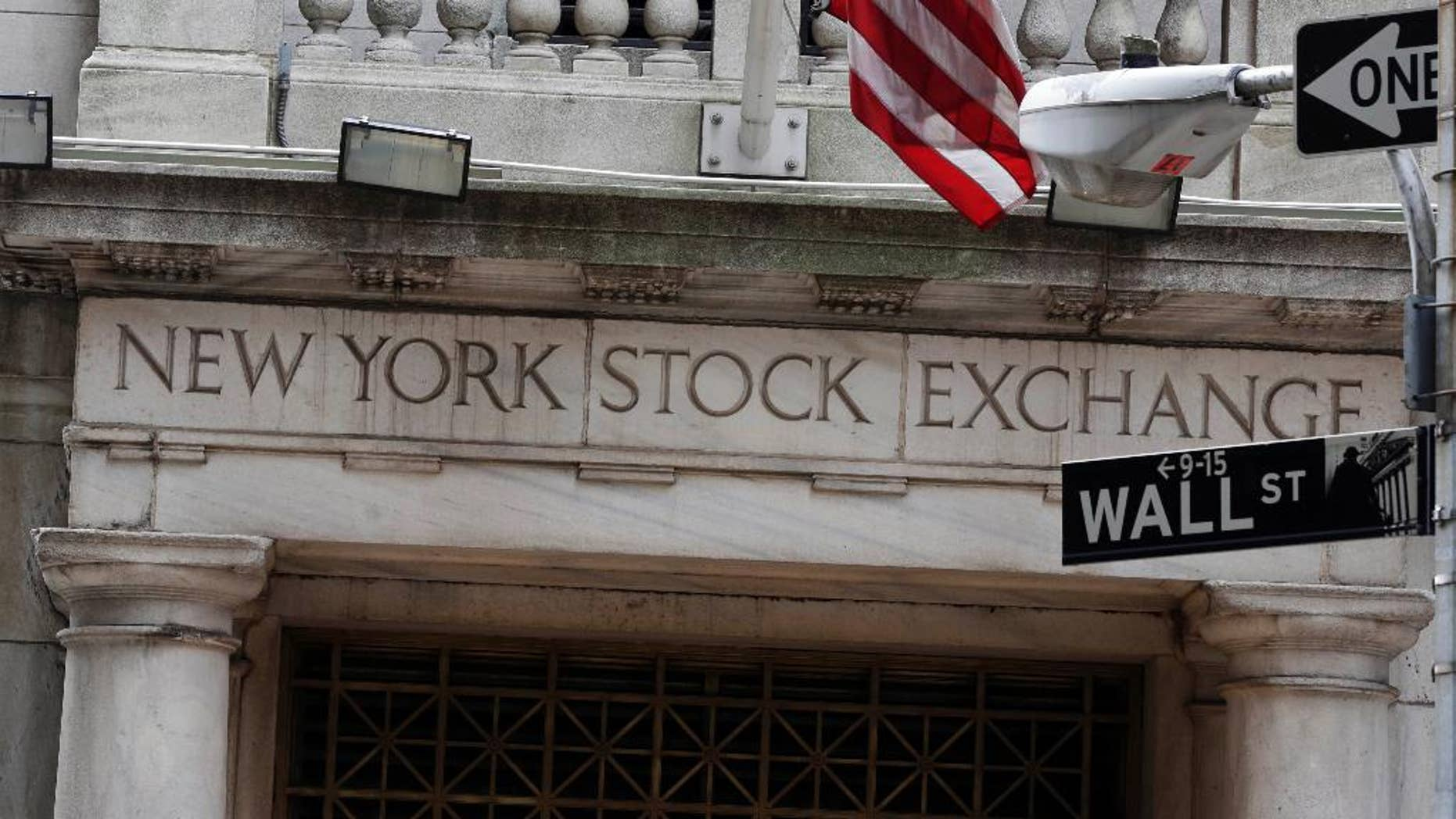 FILE - This Thursday, Oct. 2, 2014, file photo, shows the Wall Street entrance of the New York Stock Exchange. U.S. and global stocks fell Tuesday, Dec. 30, 2014, as investors closed their positions ahead of the New Year and amid concern over political uncertainty in Greece. (AP Photo/Richard Drew)