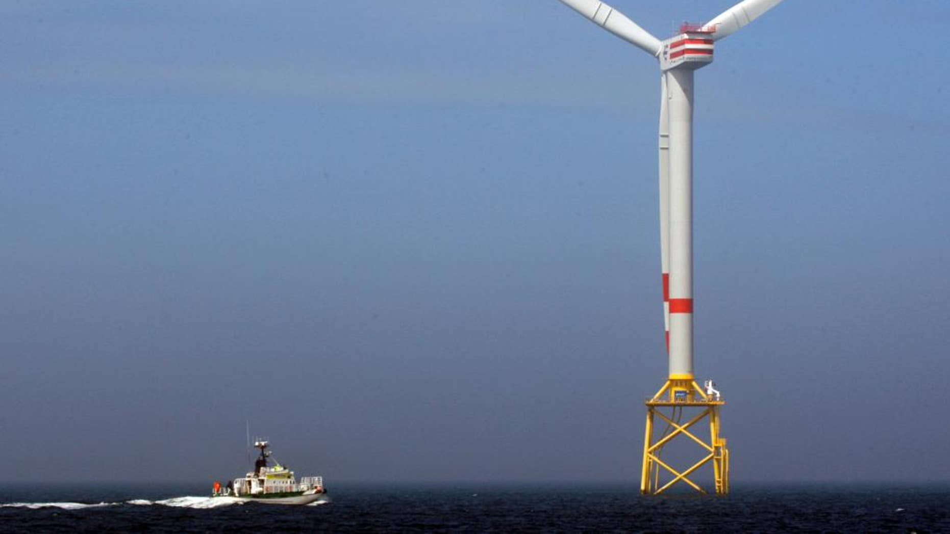 FILE - In this April 26, 2010 file photo a boat approaches a German windmill offshore power plant in the North Sea, 45 km off the coast of Norddeich.  (AP Photo/Frank Augstein, file)