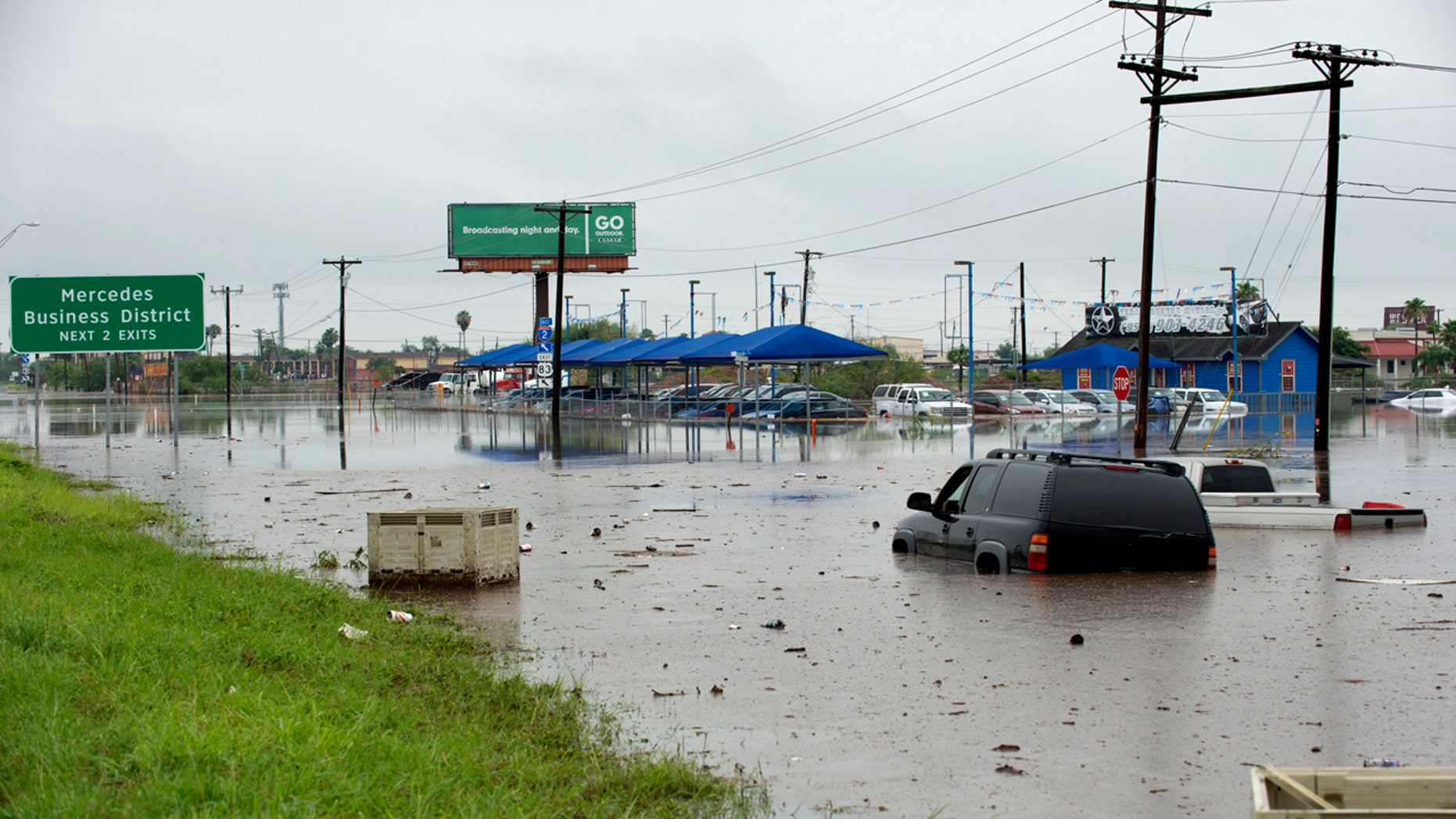 Abandoned vehicles sit in sewage-tainted floodwater Wednesday, June 20, 2018, near Mercedes, Texas.