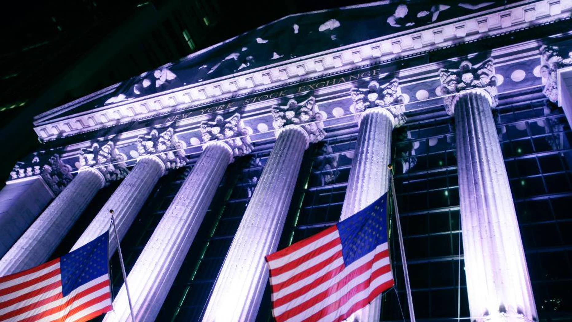 In this Wednesday, Oct. 8, 2014 photo, American flags fly in front of the New York Stock Exchange. U.S. stocks were barely higher in early trading Monday, Dec. 29, 2014, as Wall Street winds down the year in this holiday-shortened week. (AP Photo/Mark Lennihan)
